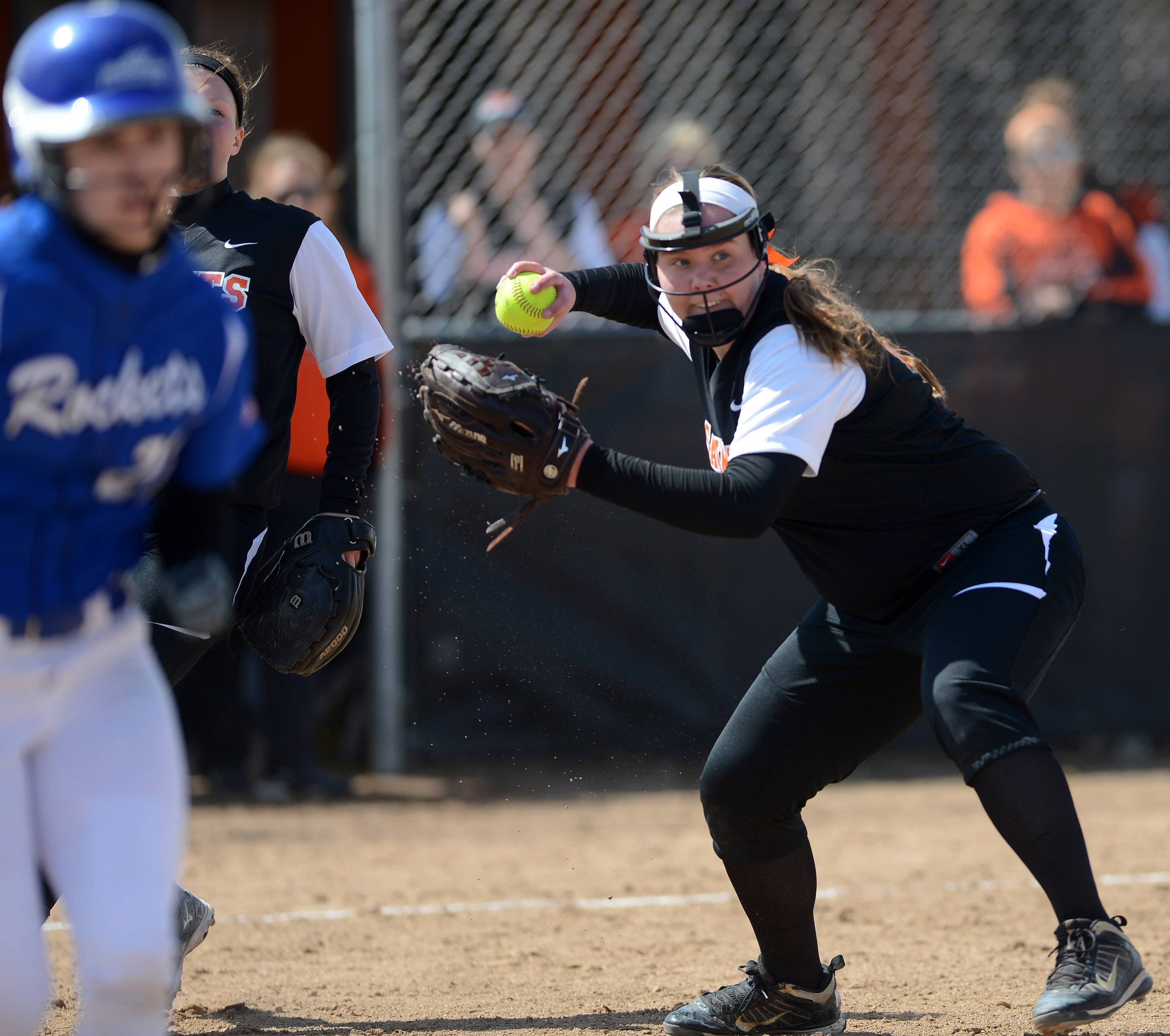 St. Charles East pitcher Haley Beno fields a bunt and fires to first to throw out Burlington Central's Kelly Wiater during Monday's game in St. Charles.