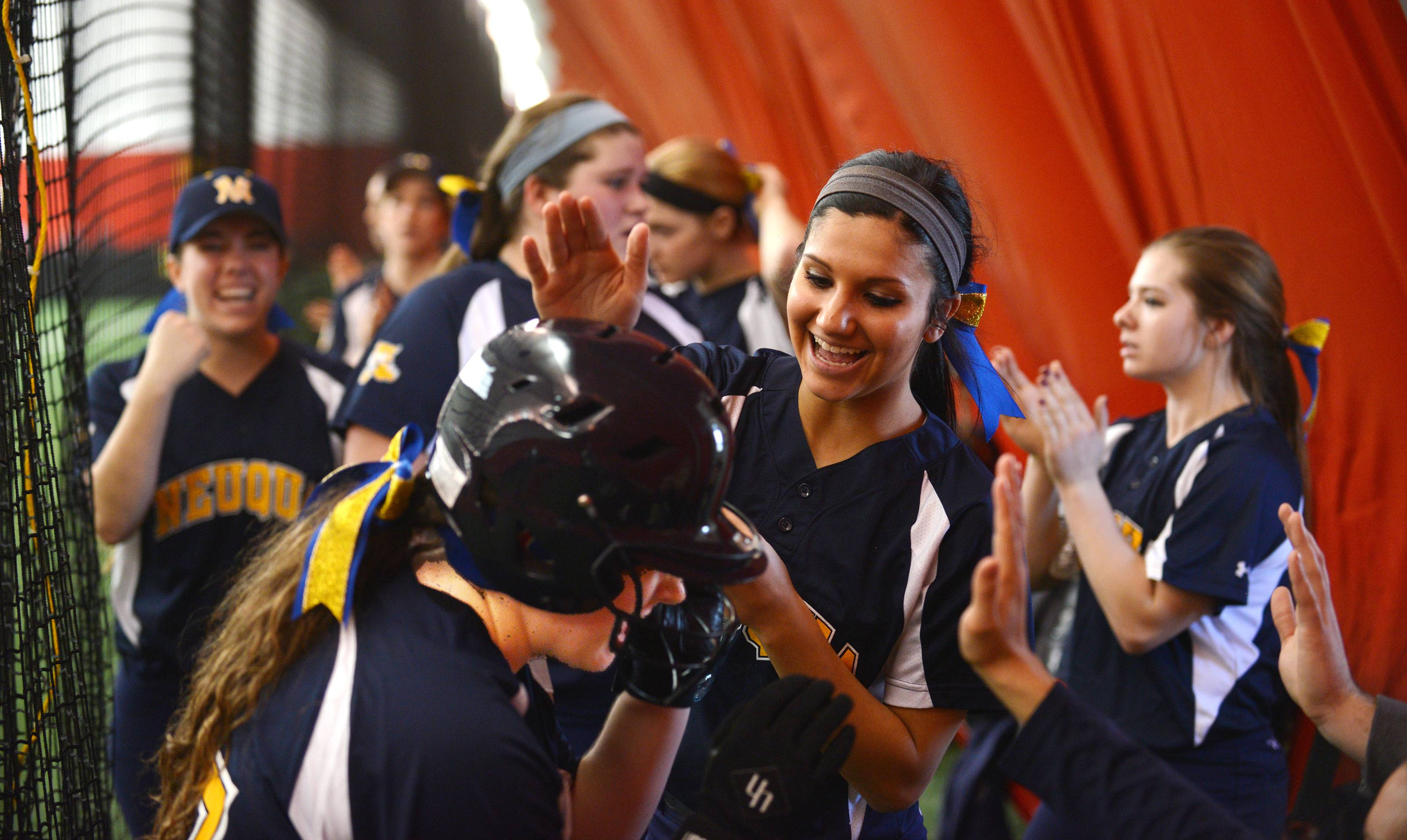 Benet played Neuqua Valley Monday, March 31 in indoor softball action in Rosemont. Neuqua Valley's Dominica Lange, foreground, is congratulated by teammates after sliding into home with the go-ahead run in the 4th inning.
