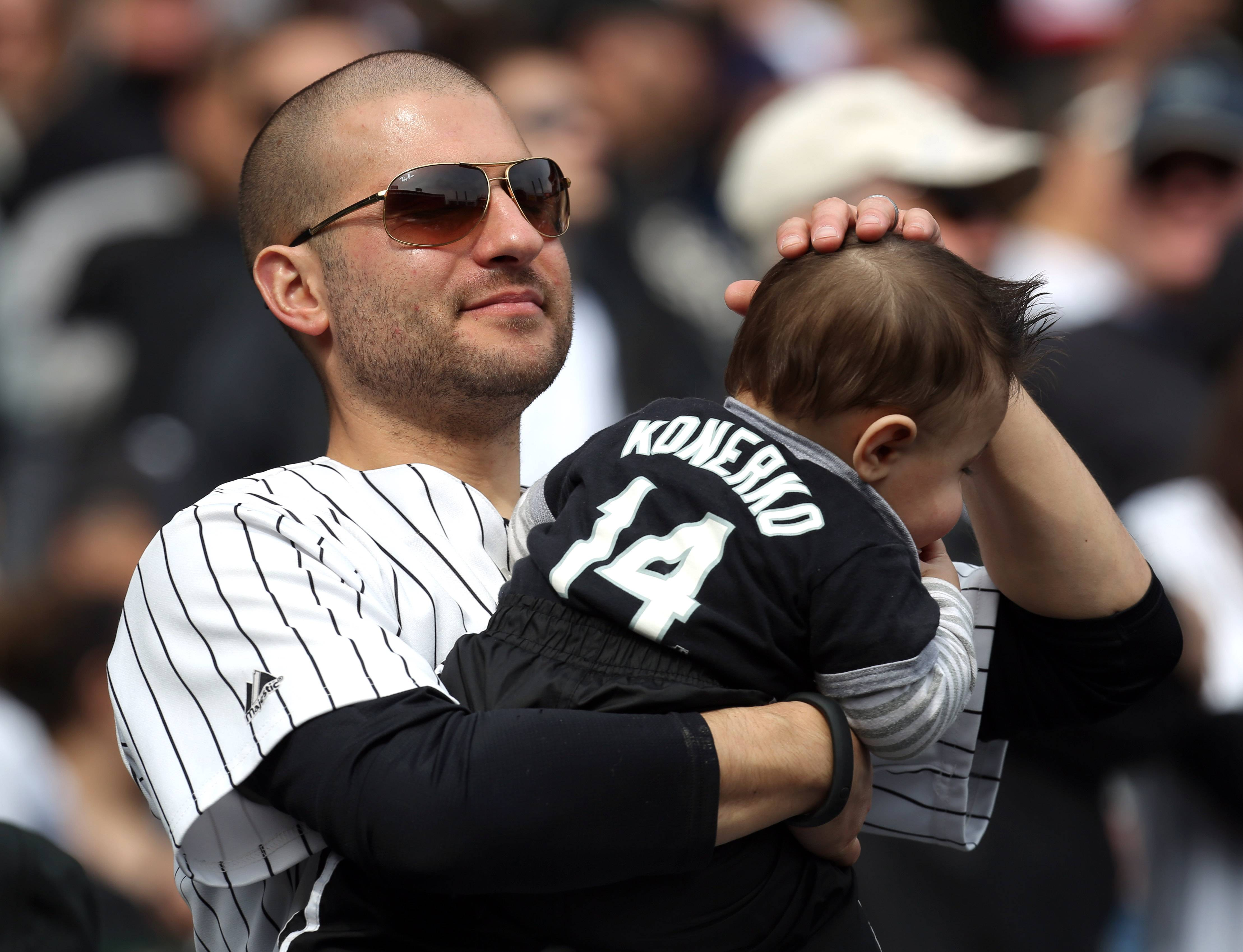 A fan holds his infant son who is wearing a Paul Konerko Jersey.