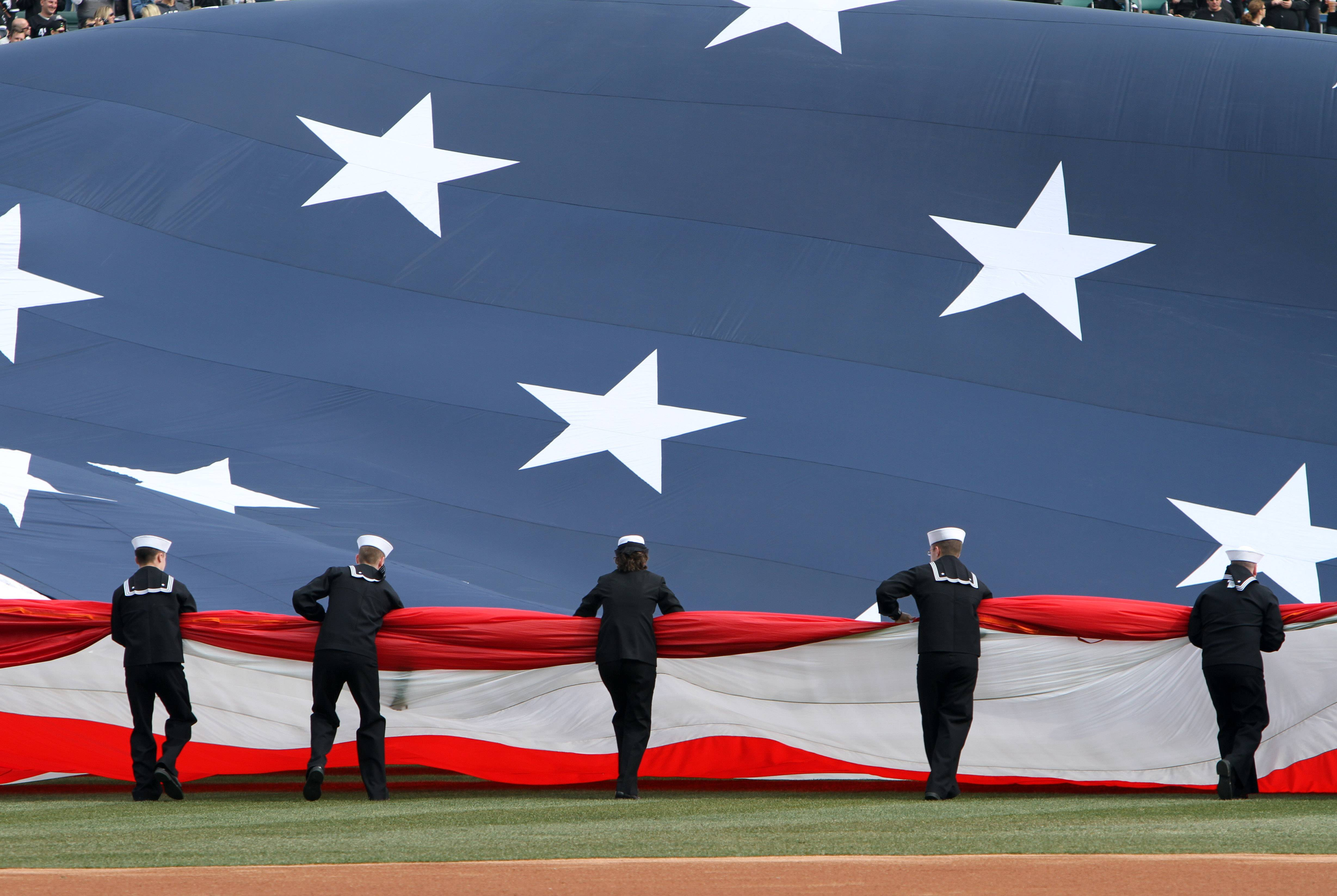 Sailors from Great Lakes Naval Base unfurl a giant American flag.