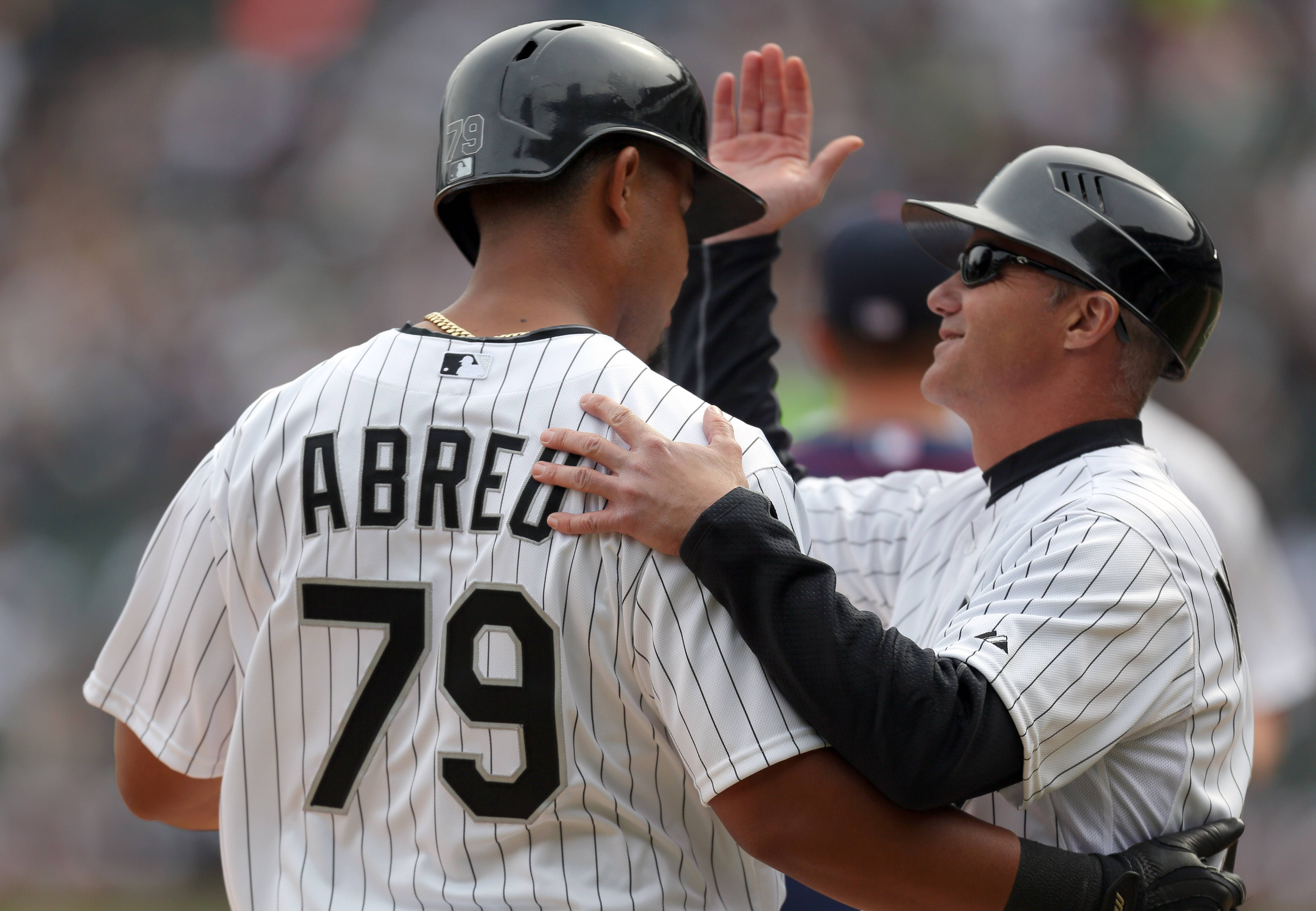 Chicago White Sox third base coach Joe McEwing congatulates Chicago White Sox first baseman Jose Abreu after a hit.