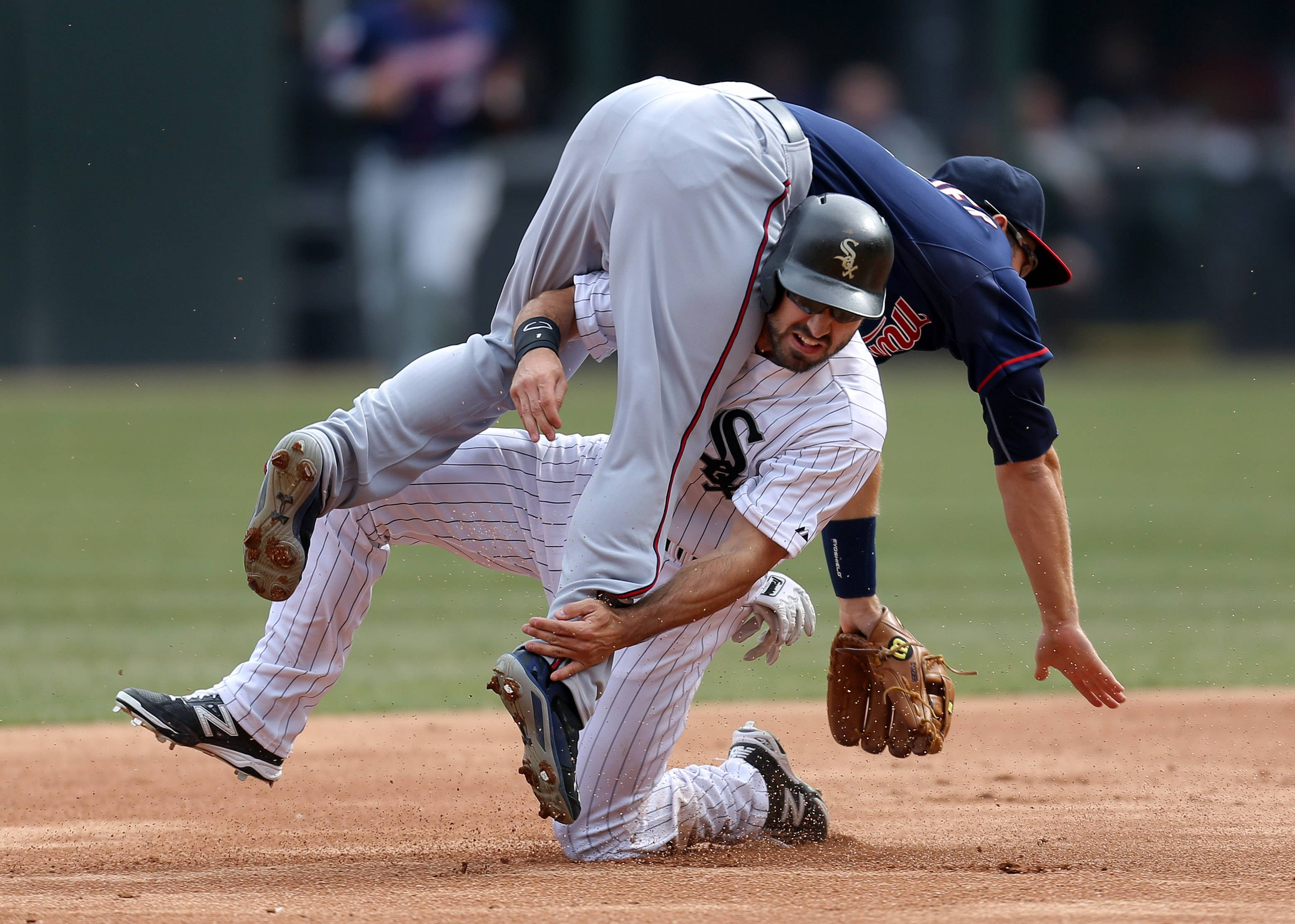 Chicago White Sox left fielder Adam Eaton gets tangled up with Minnesota Twins second baseman Brian Dozier.
