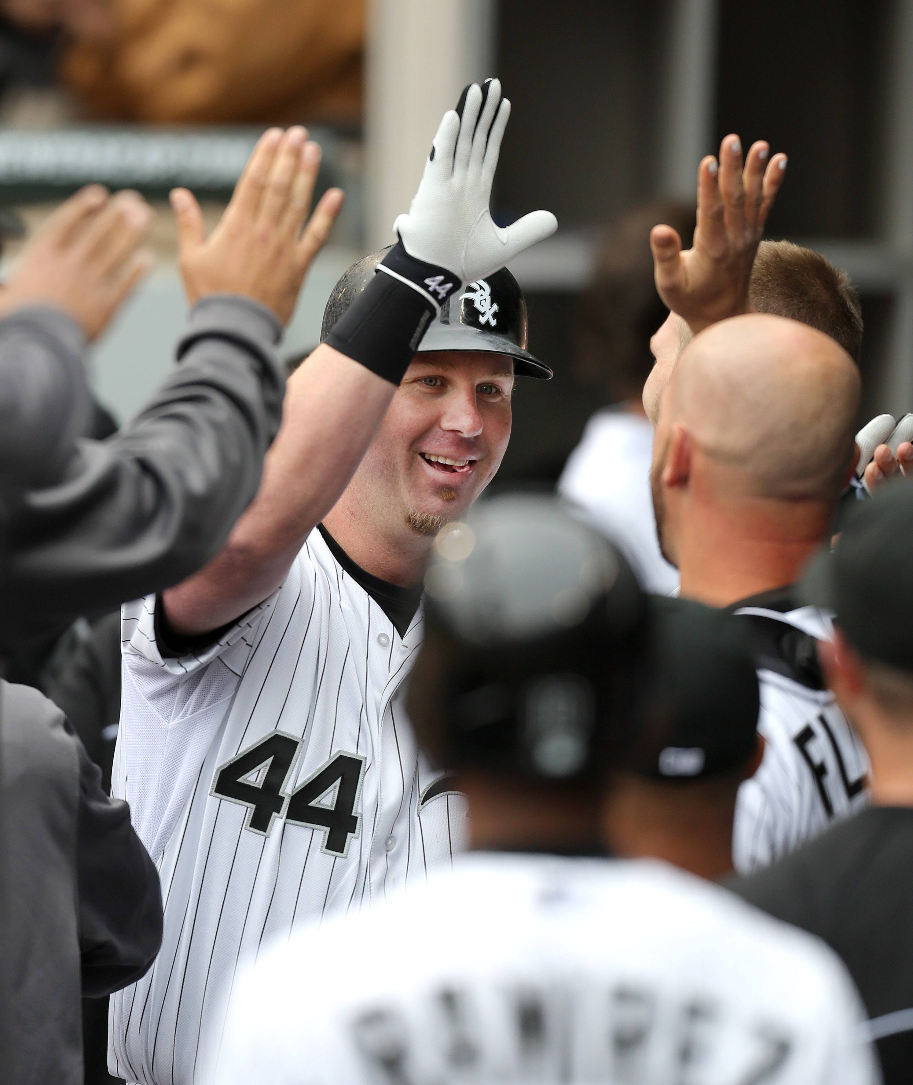 Chicago White Sox designated hitter Adam Dunn high-fives teammates after Conor Gillaspie scored.