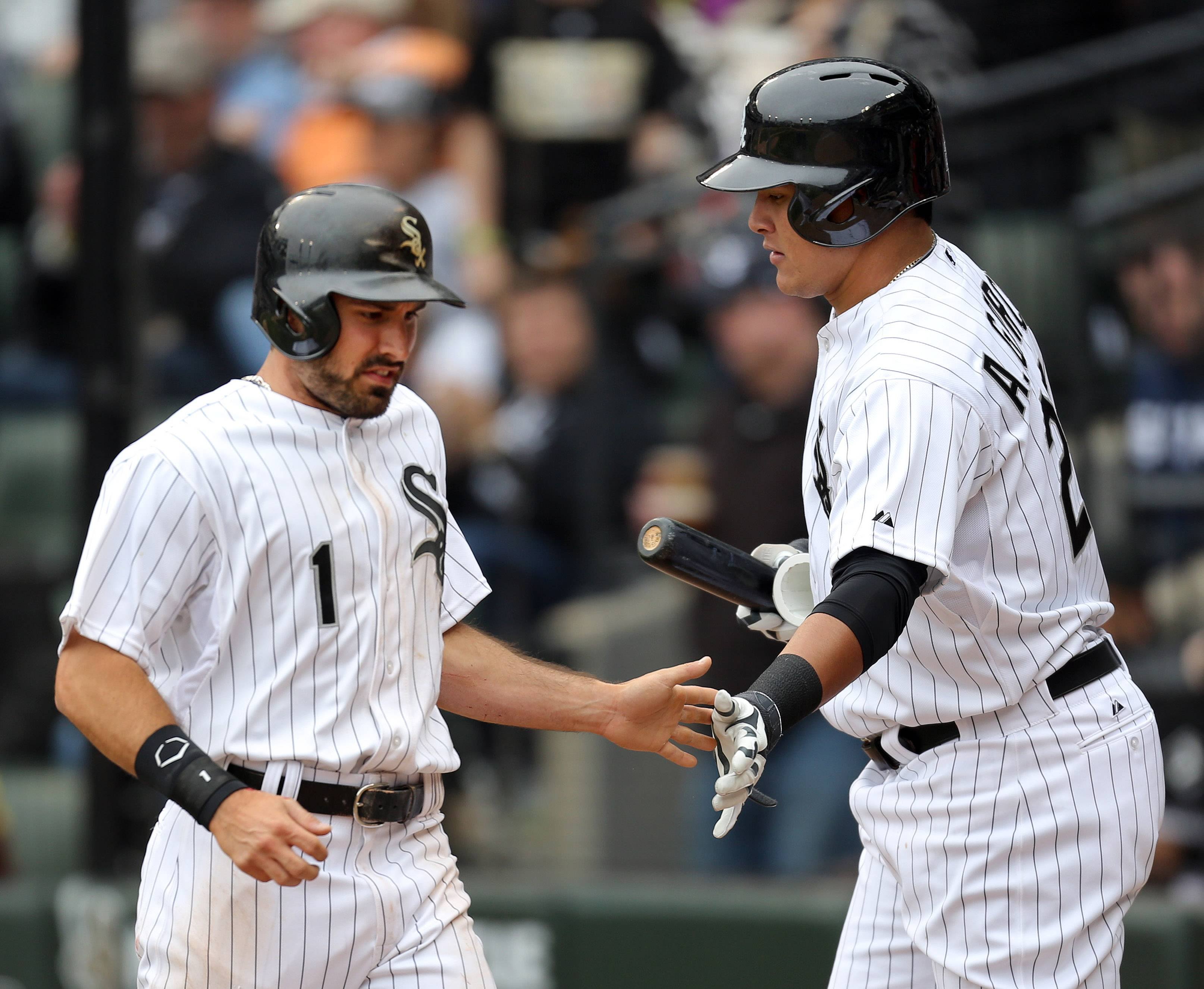 Chicago White Sox left fielder Adam Eaton high-fives Chicago White Sox right fielder Avisail Garcia.