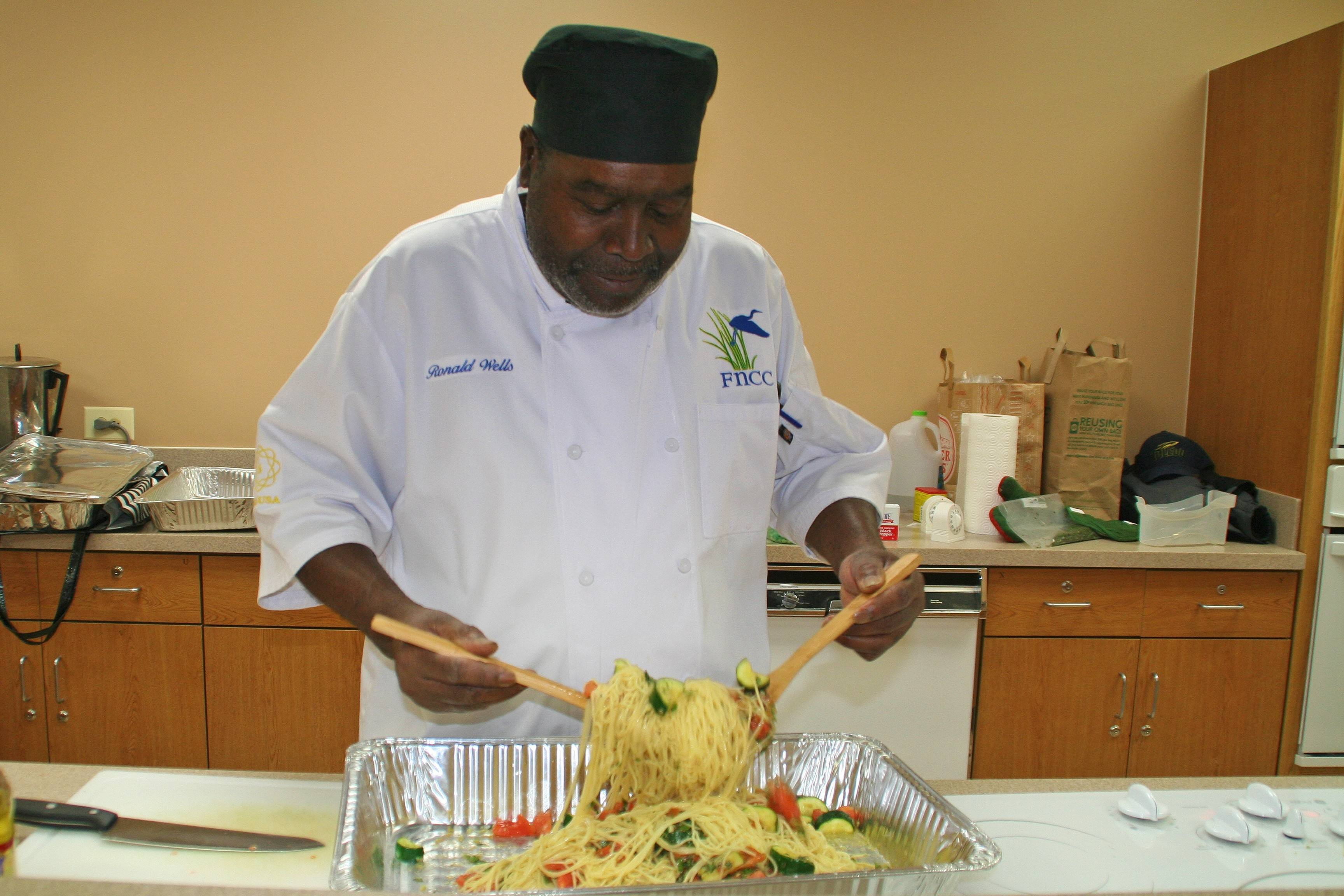 Chef Wells tosses sautéed garlic, zucchini, and tomatoes with angel hair pasta in his March 20 class at Prairie Lakes.