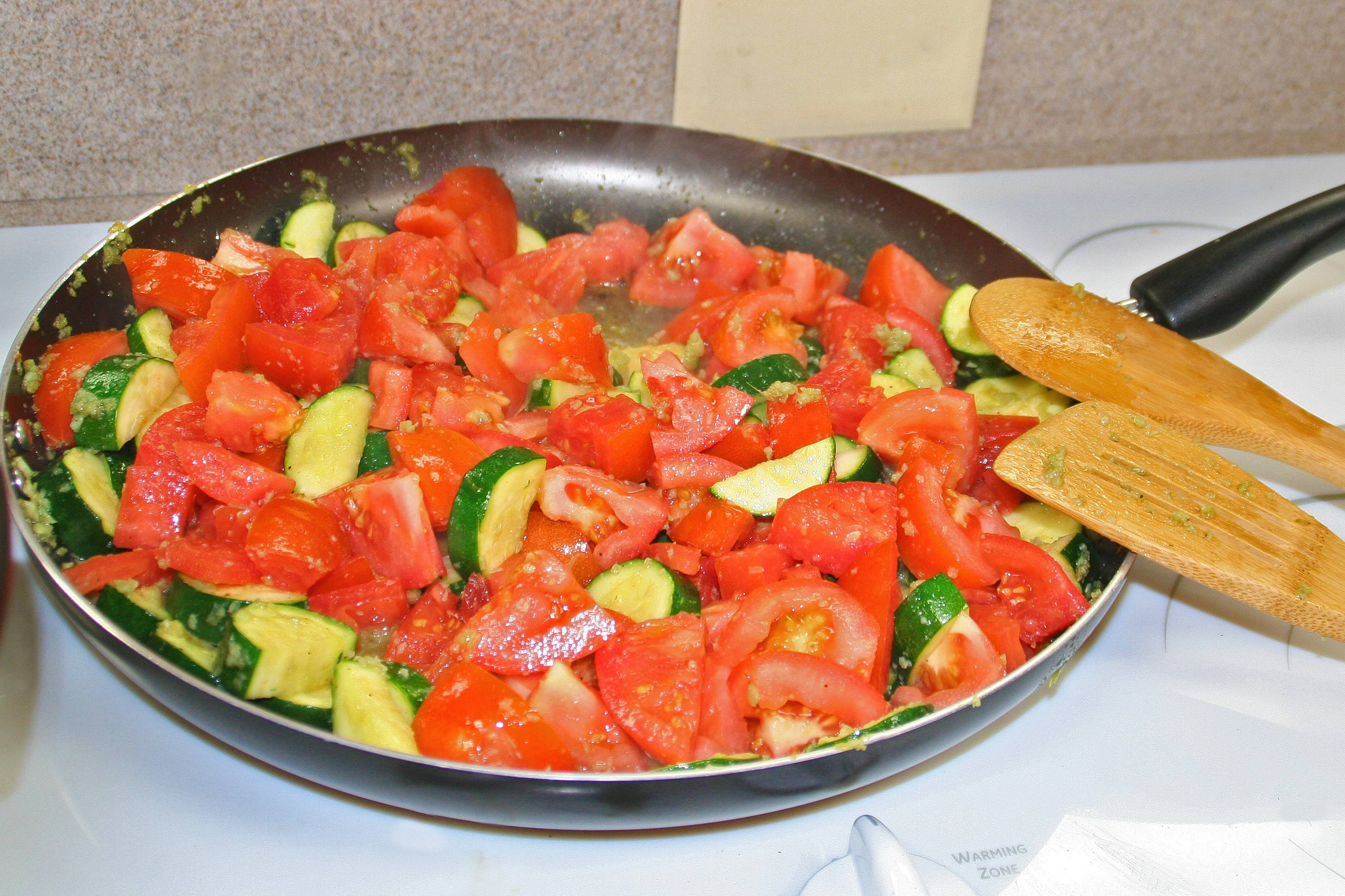 Tomatoes, garlic, and zucchini sauté in olive oil.