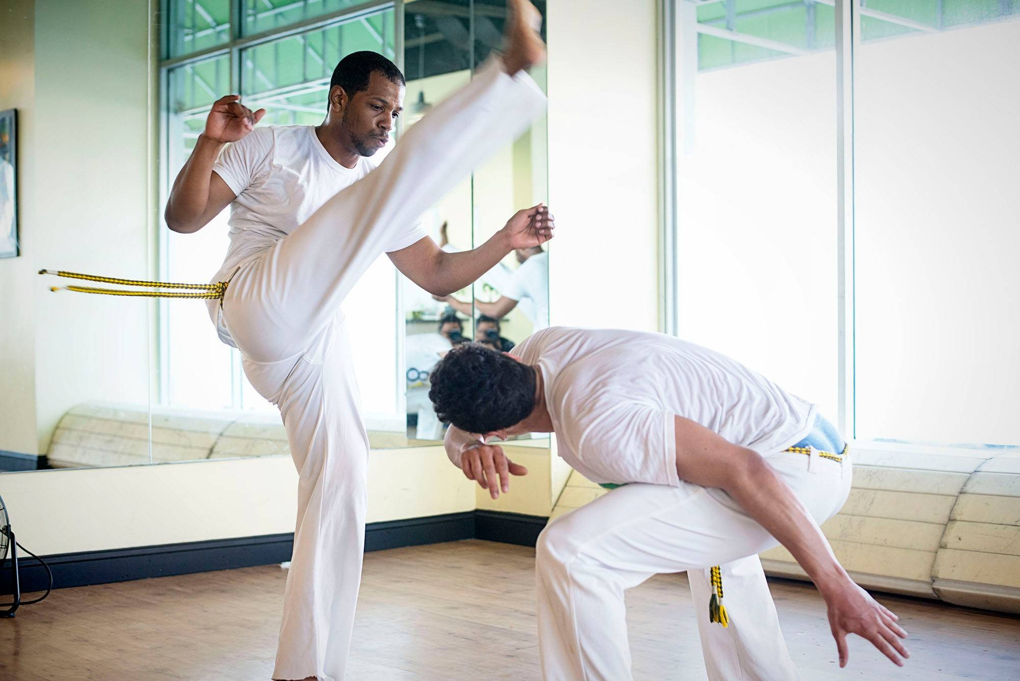Ali Ahmad, left and Amado Carsky spar in capoeira class; capoeira is accompanied by drums and singing, true to its Brazilian origins.