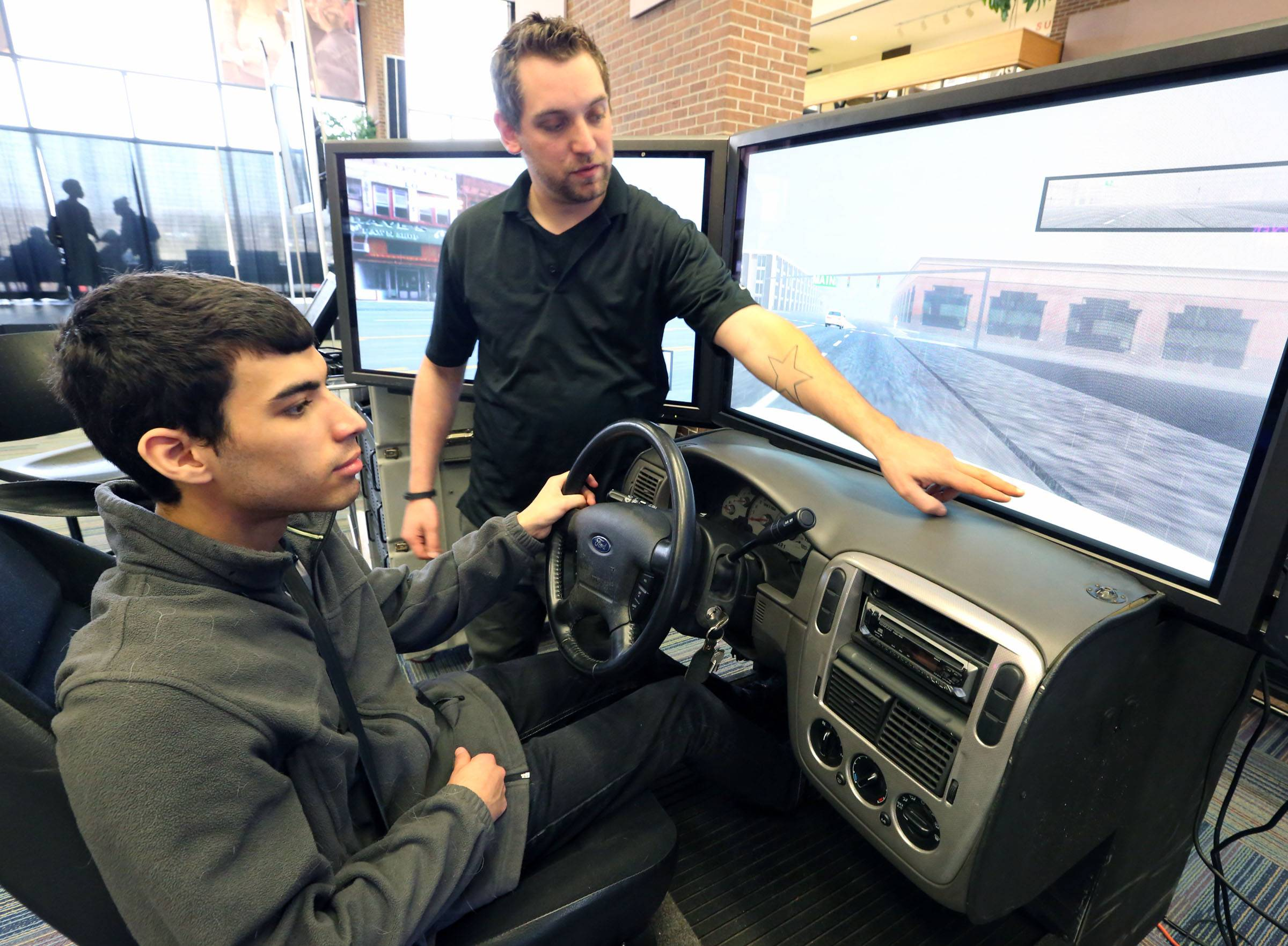Andrew Tipton, a Save a Life Tour program manager, explains to Harper student Dan Serranol how to use a drunken driving simulator at the Palatine campus.
