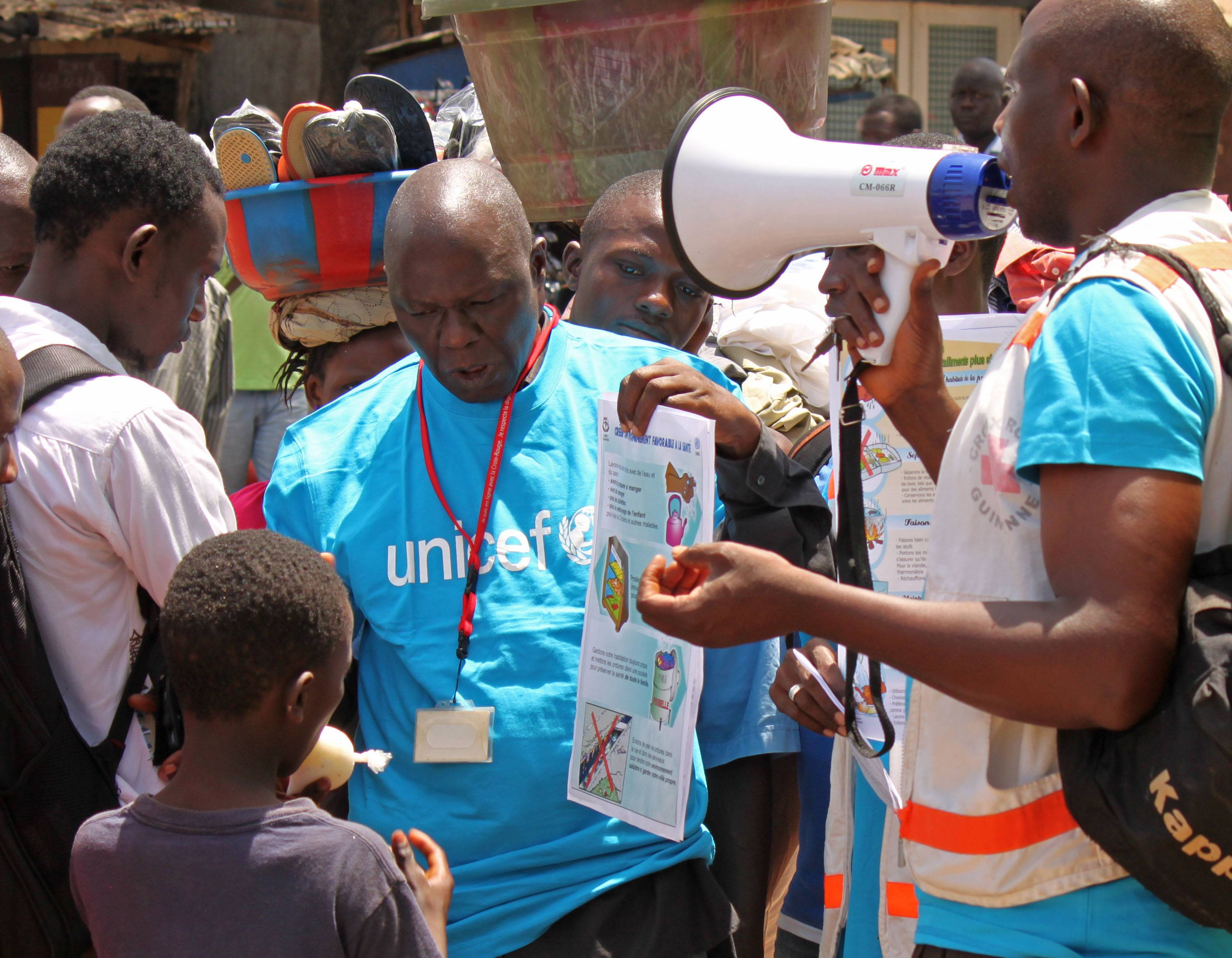 Health workers teach people Monday about the Ebola virus and how to prevent infection, in Conakry, Guinea.