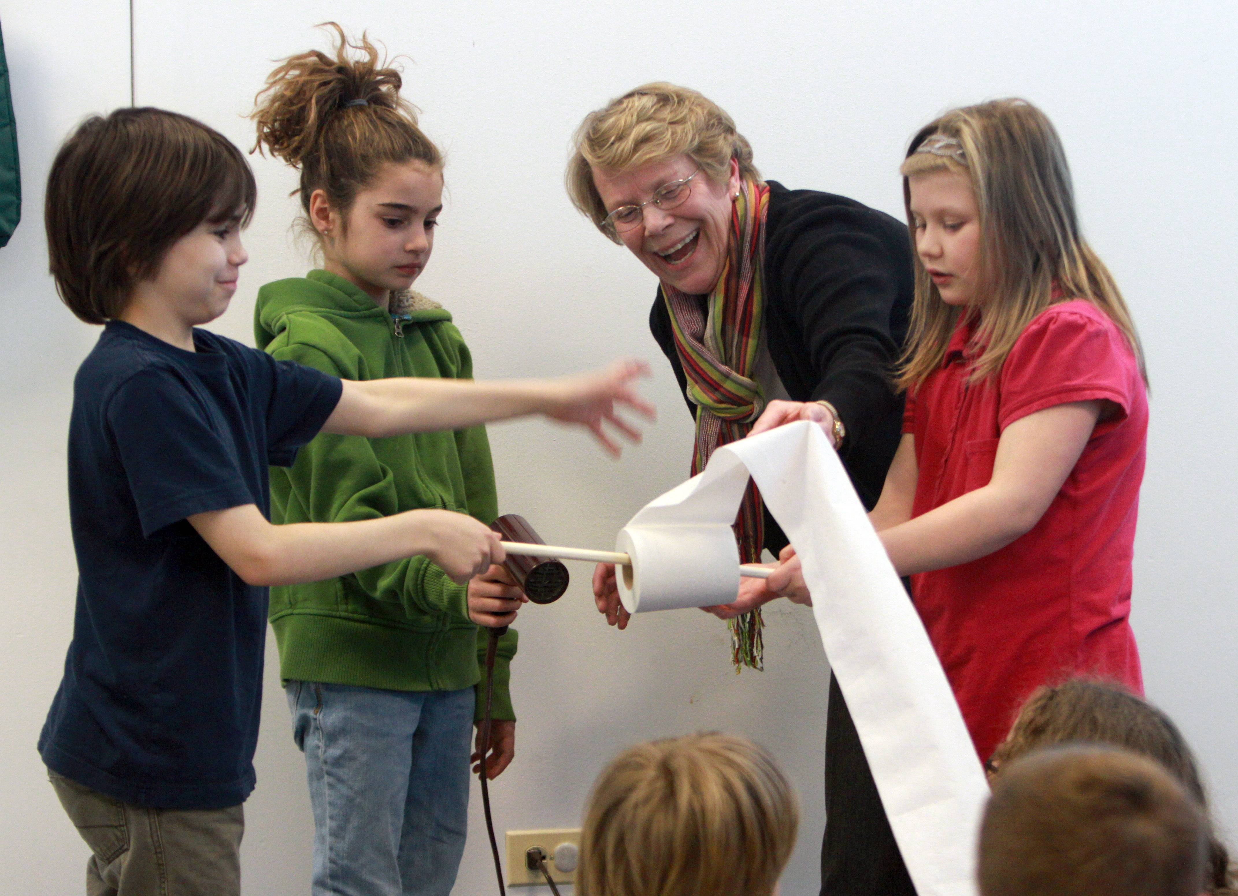 From left, Kyle Boness, 9, Cecilia Frievalt, 9, Children's Librarian Sue Ernest and Delaney Schild, 9, use a hair dryer to blow toilet paper of the roll during an April Fools' Day version of Cool Science at Grayslake Public Library Tuesday. The experiment demonstrated Bernoulli's Principal. The paper flies off the roll because the pressure beneath the paper is higher than on top.