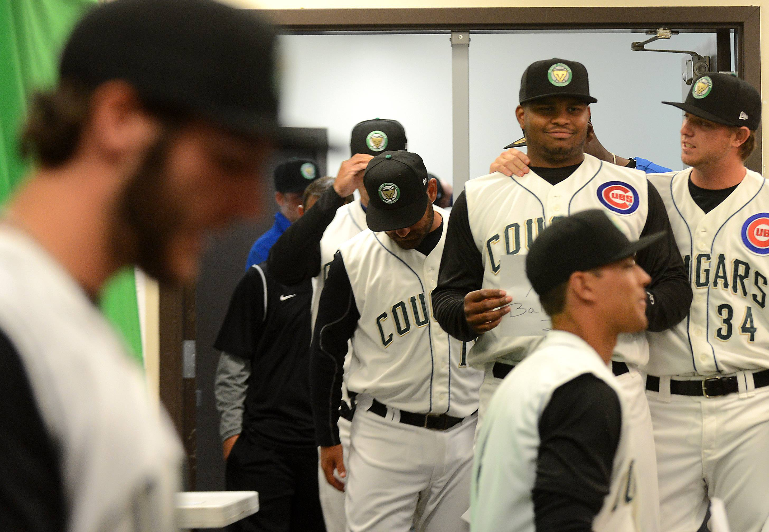 Paul Blackburn, right, puts an arm around a bemused Yasiel Balaguert as they wait to have their picture taken during Media Day for the Kane County Cougars Tuesday in Geneva.