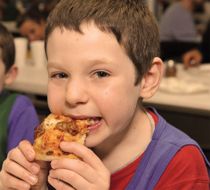 Quentin Road Christian School student Josh Huss digs into pizza in Lake Zurich. The school is holding its 30th annual Pizza Blast in April.