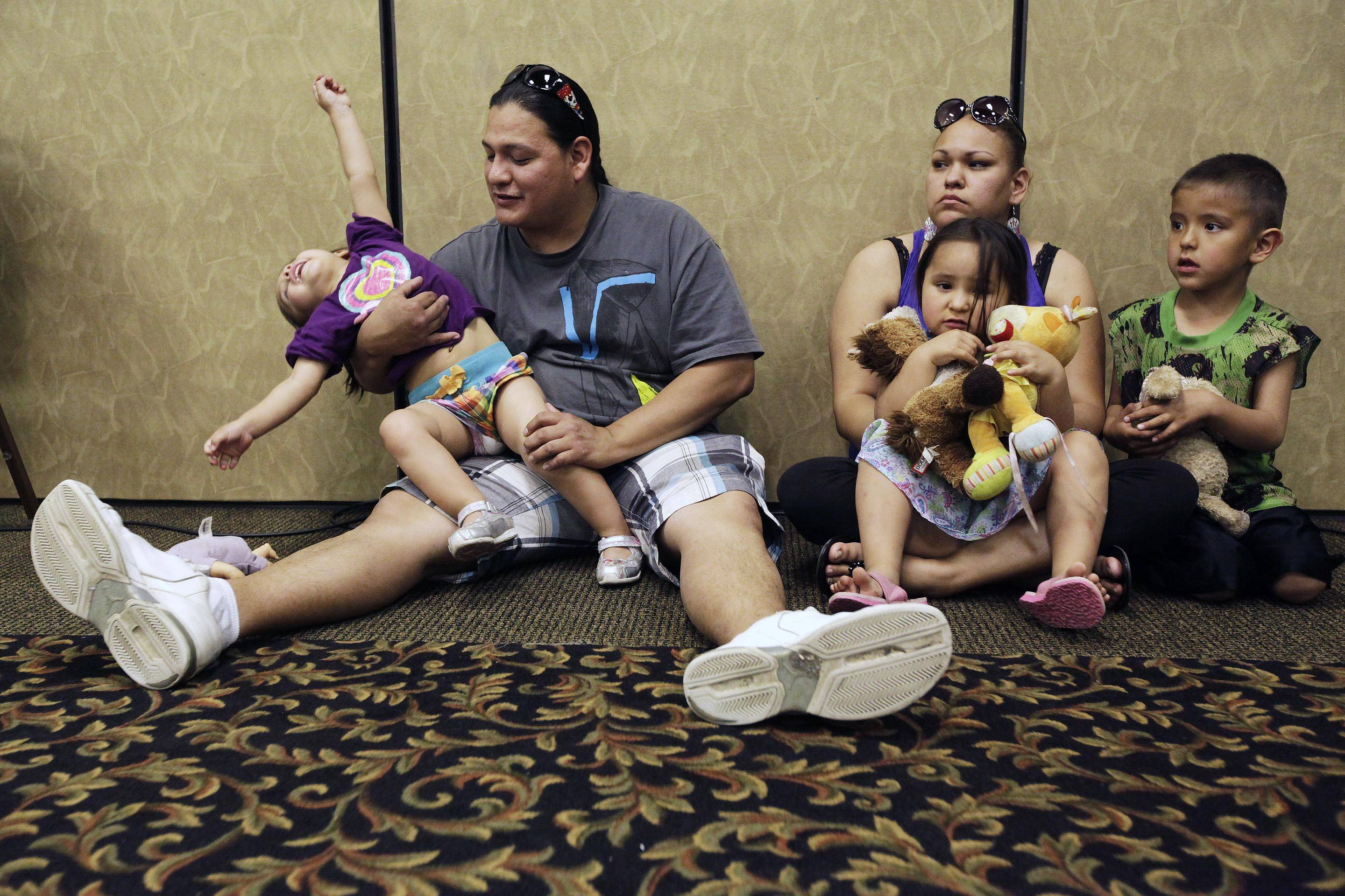 Elijah Bearsheart, left, holds his daughter, Keanala, 1, as he sits with his family, Kehala Diserly, Kiari Diserly, 3, and Yamni Pederson, 5, as they listen to testimony during the Indian Child Welfare Act summit in Rapid City, S.D., in May 2013.