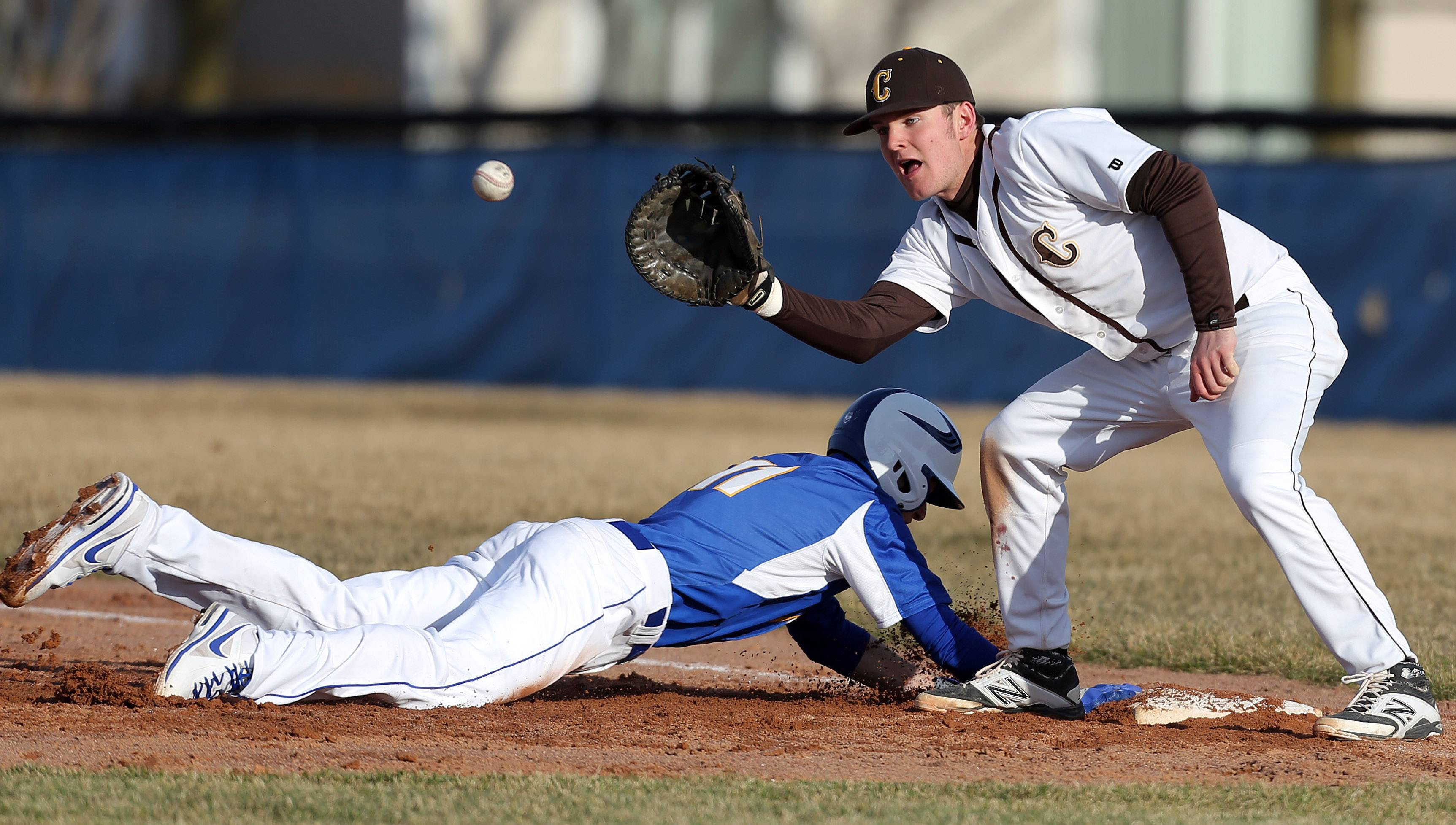 Warren's Chris Mathieu, left, dives back to first, beating the tag by Carmel's Andrew Wienke on Tuesday at Warren.