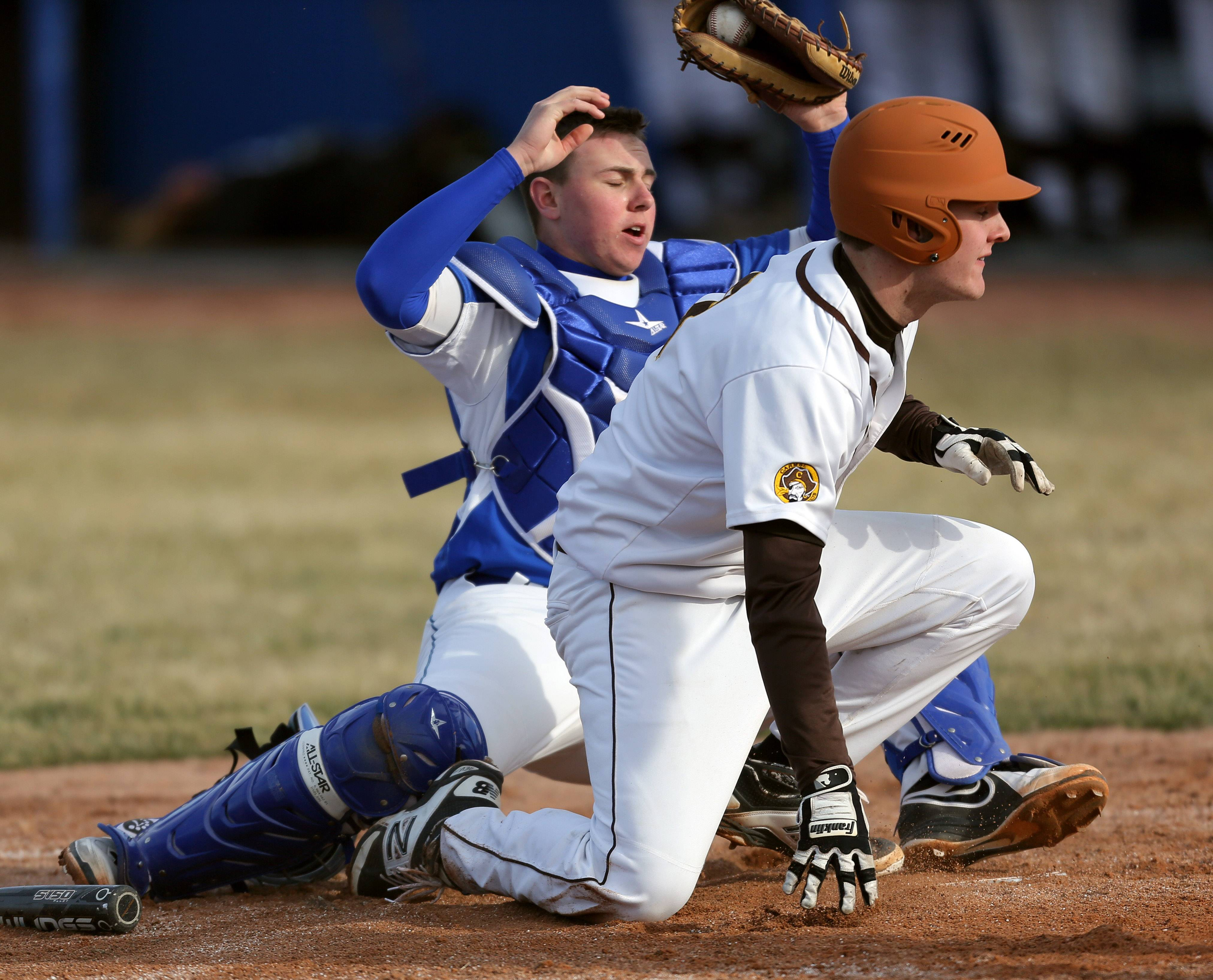 Carmel's Andrew Wienke, right, is safe at home after a collision with Warren catcher Andrew Nickell on Tuesday at Warren.