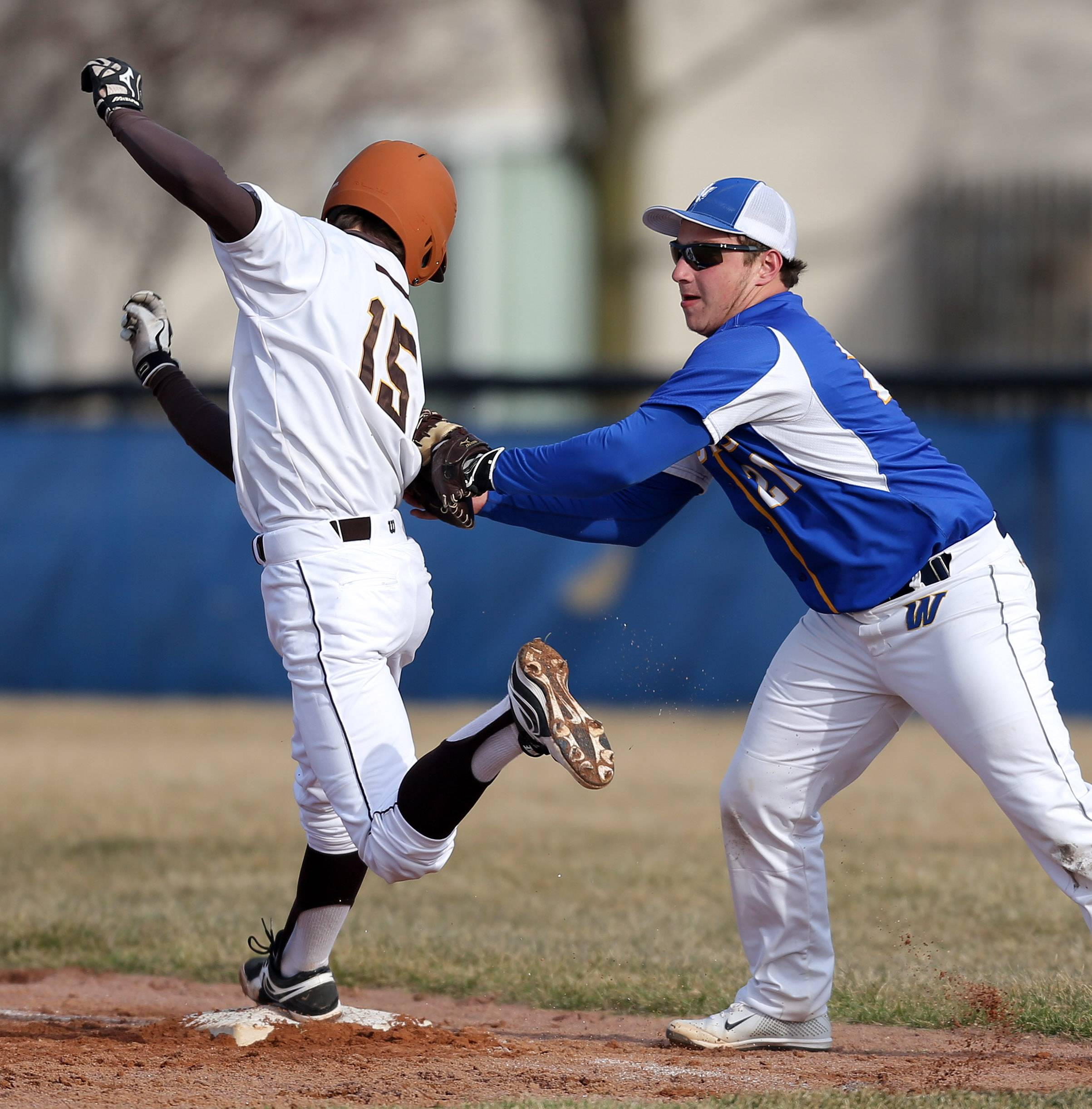 Carmel's Billy Winegard, left, is tagged out by Warren first baseman Stephen Binstock on Tuesday at Warren.