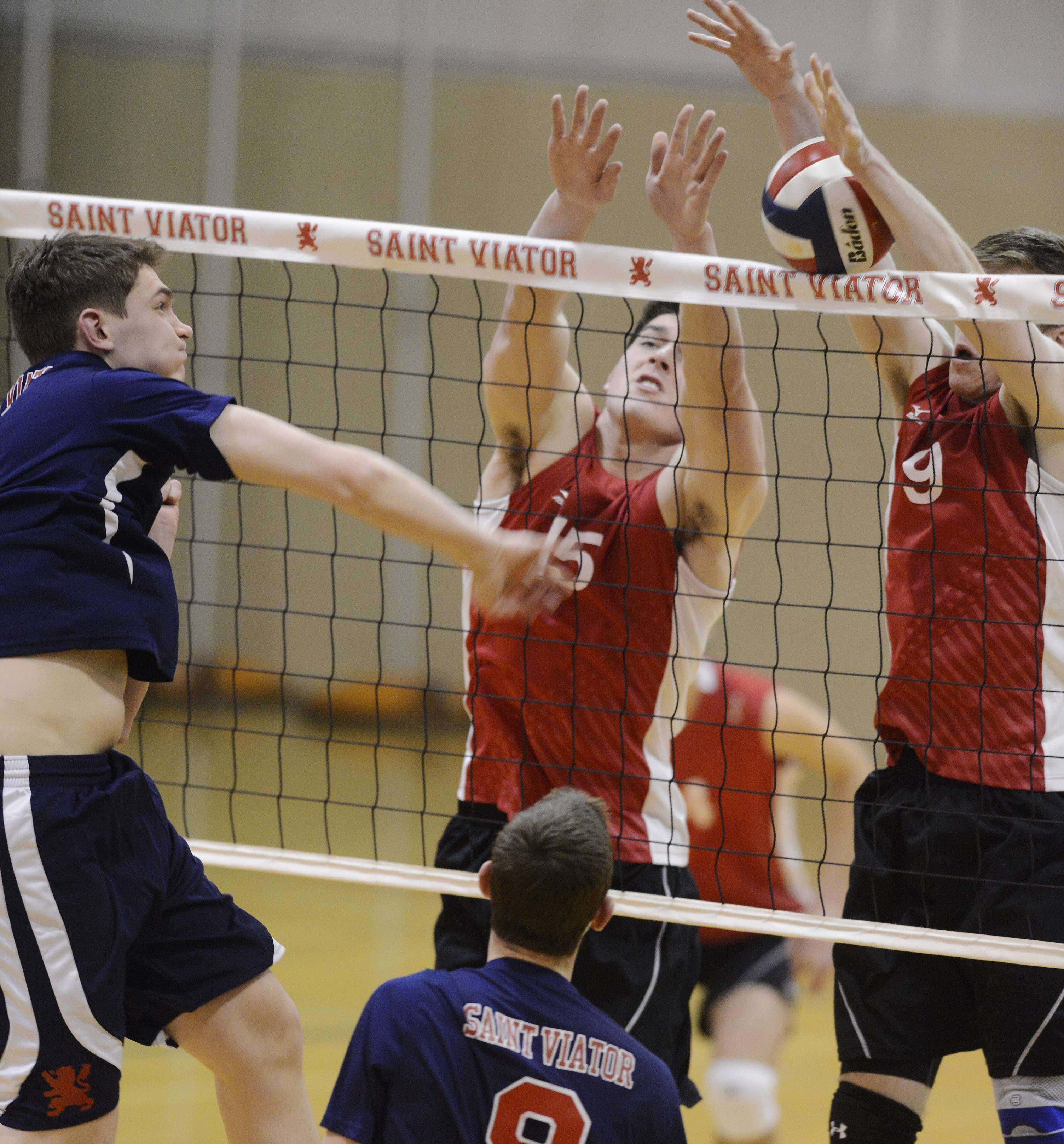 A kill attempt by St. Viator's Ryan Schiller, left, is blocked at the net by Barrington's Colin Castagna, middle, and Connor Wright during Tuesday's boys volleyball game in Arlington Heights.
