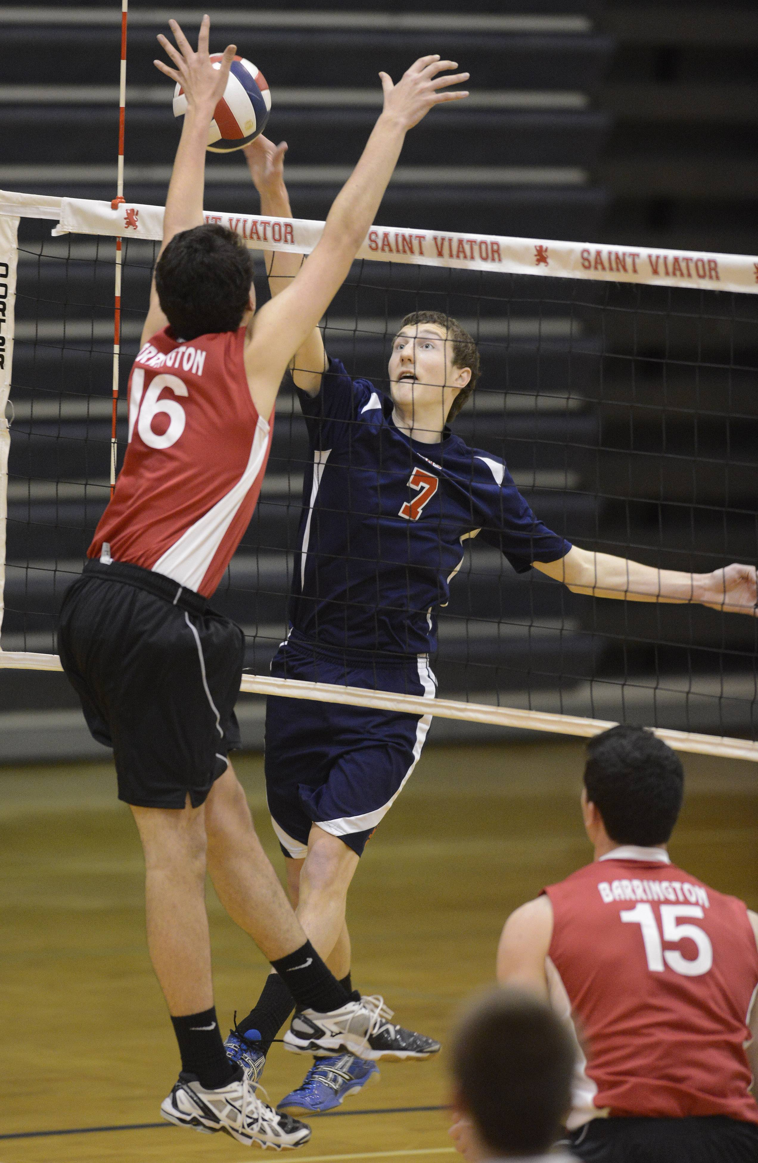 St. Viator's Ethan Wolf, right, tries to get the ball past Barrington's Mike Amato during Tuesday's boys volleyball game in Arlington Heights.