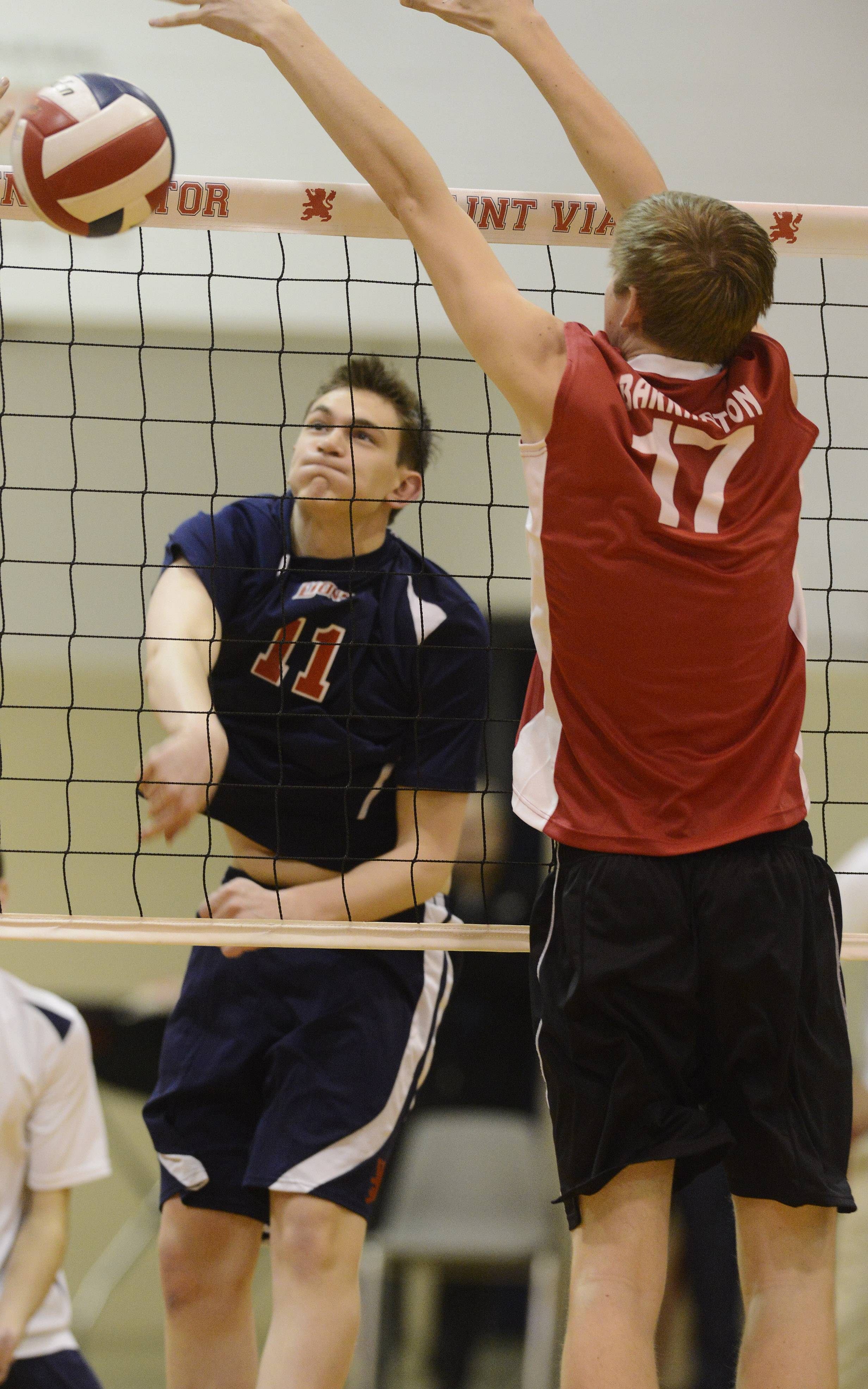 St. Viator's Ryan Schiller leaps for a kill as Barrington's Ethan Carroll, right, tries to block the ball at the net during Tuesday's boys volleyball game in Arlington Heights.