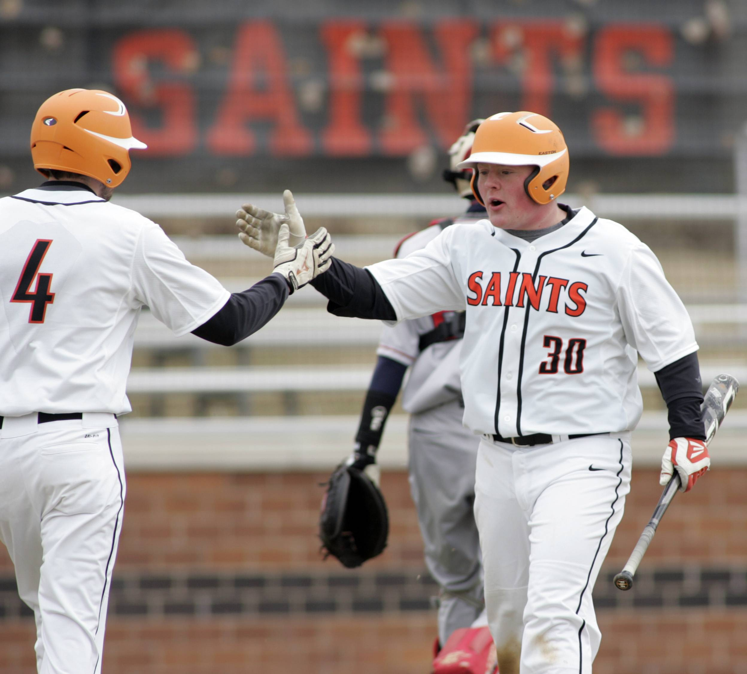Saints' Charles Alex Abate, 4, greets Ben Smith at the plate after Smith scored on a double by Adam Rojas during the Saints' win over West Aurora in St. Charles on Tuesday.