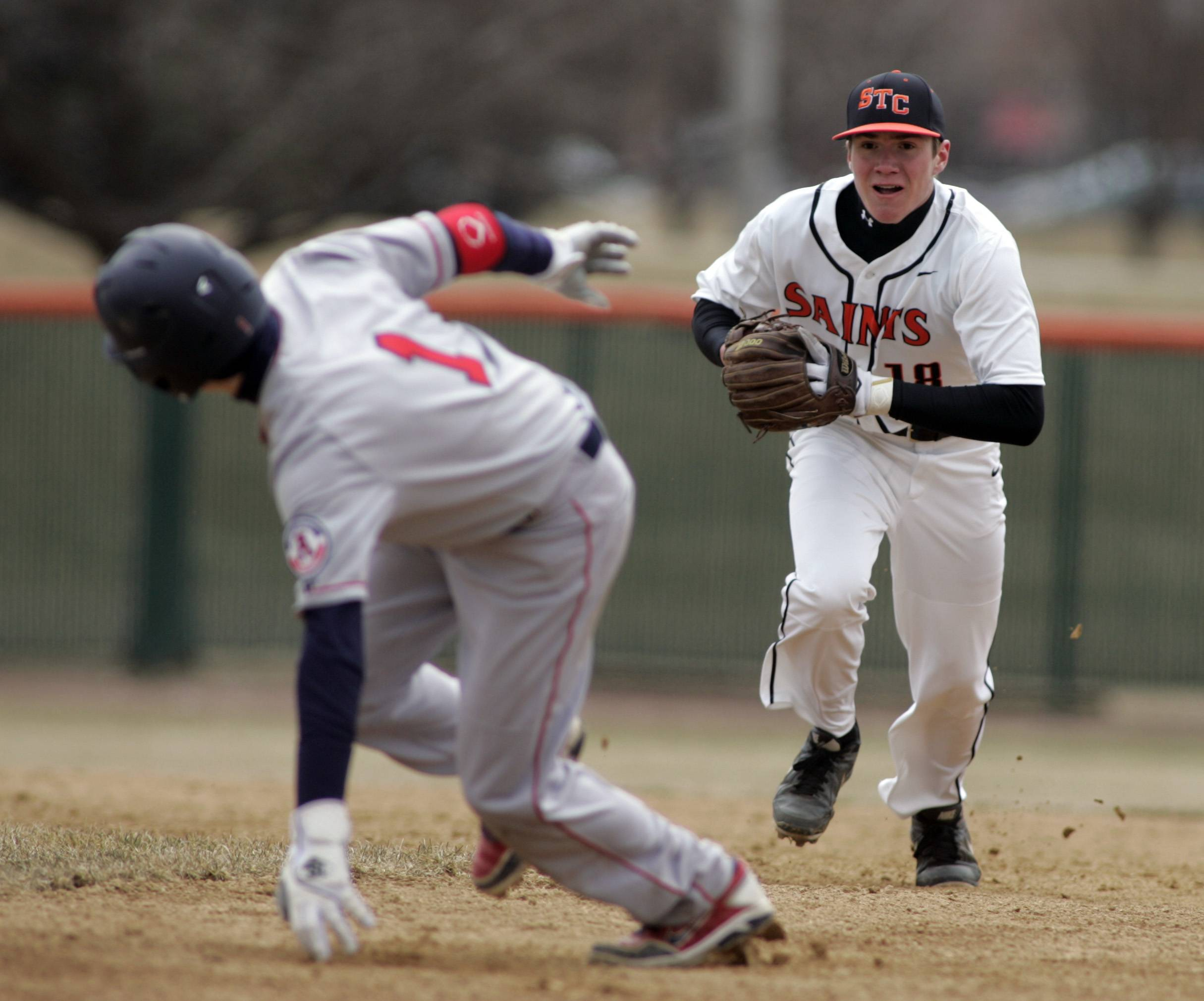 Saints' Jake Milosch, 18, pressure West Aurora's Michael Golich, 1, during a run down Tuesday.