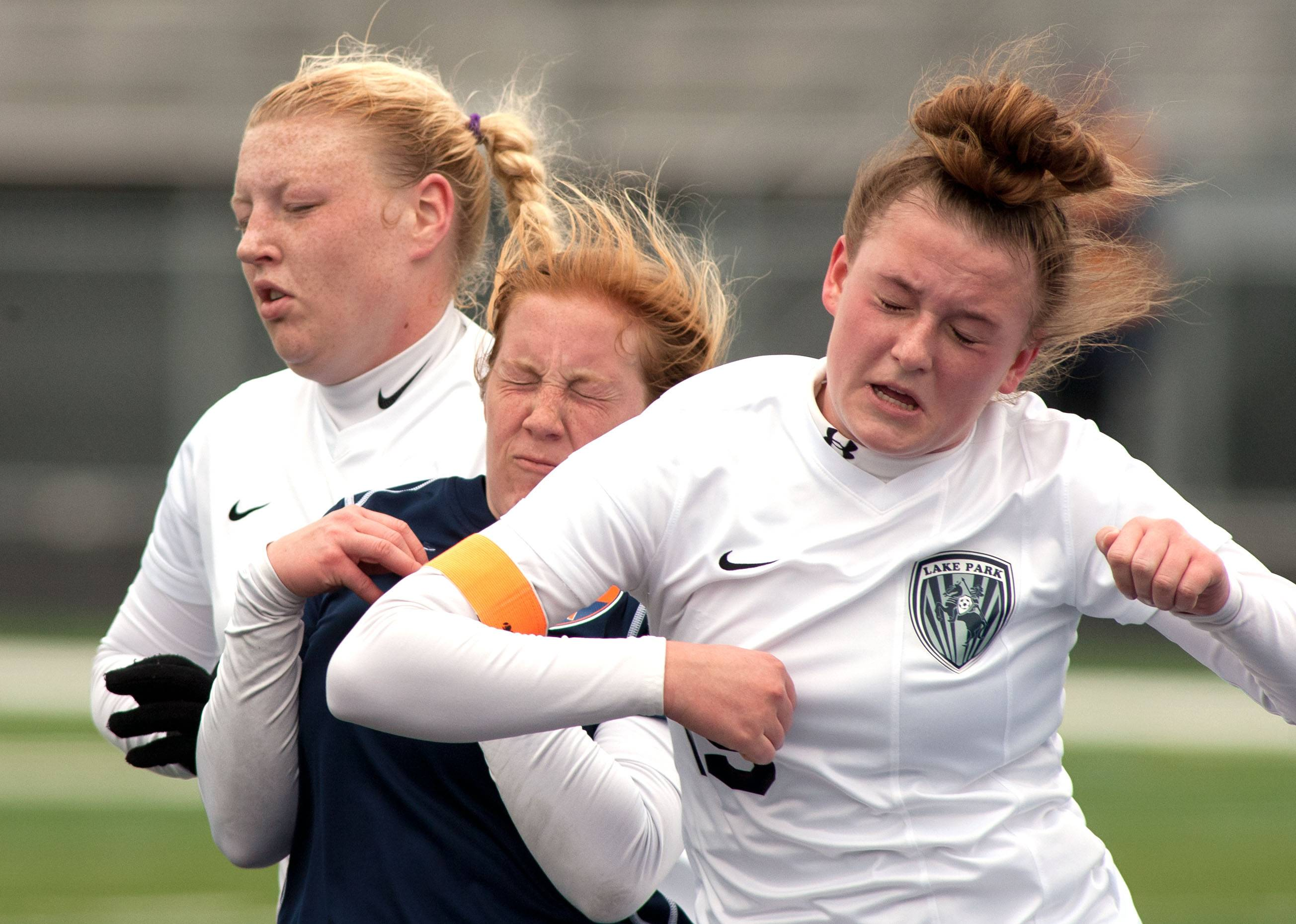 Buffalo Grove's Kelli Zickert, center, battles Lake Park's Casey Harris during girls soccer action in Roselle.