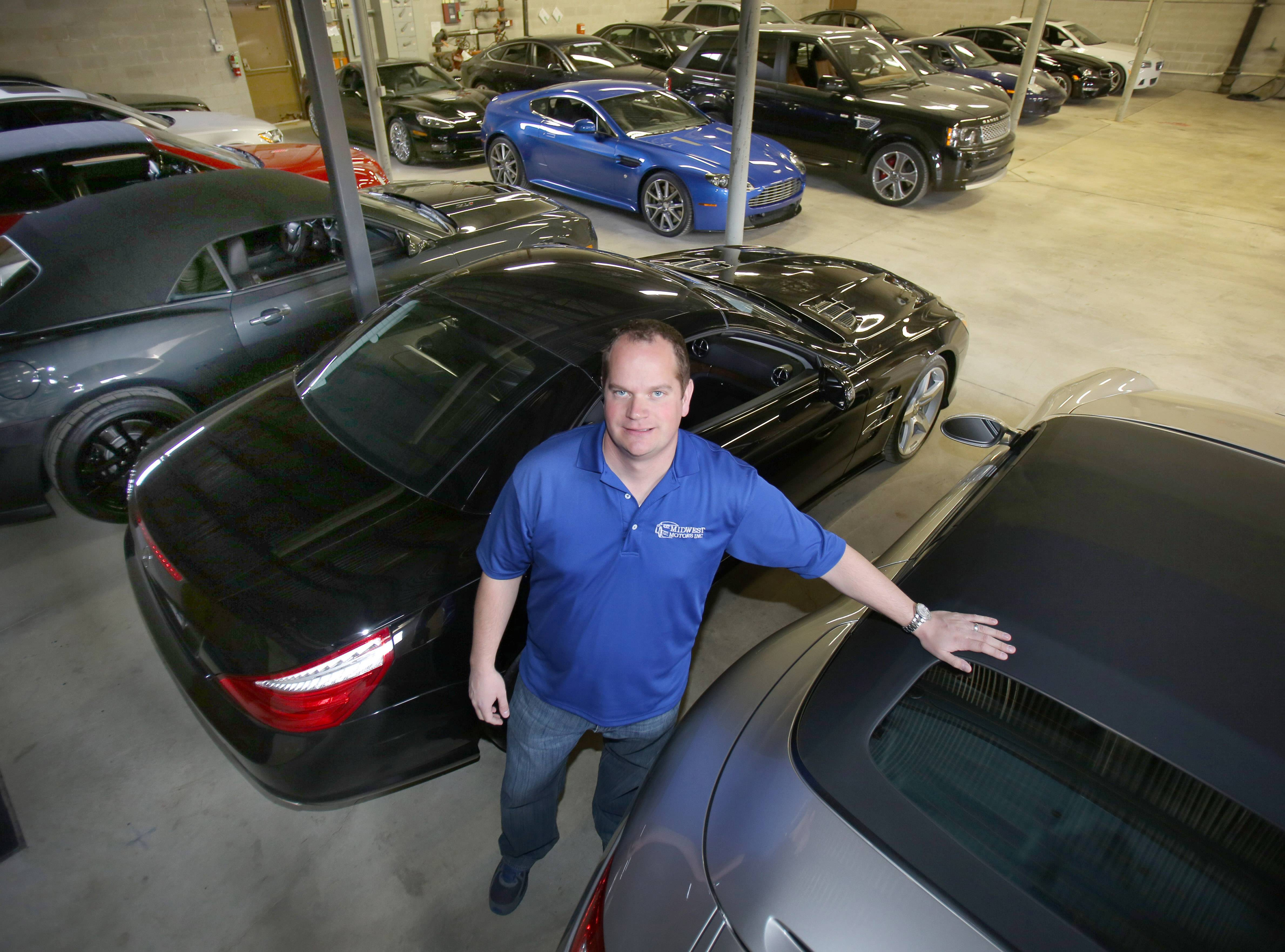 Benjamin Ripstein, owner of Midwest Motors Inc. in Lake Zurich, with high-end luxury cars Wednesday in a temporary location on Oakwood Road. A fire last week forced him out of his building on Cortland Drive on the village's west side.