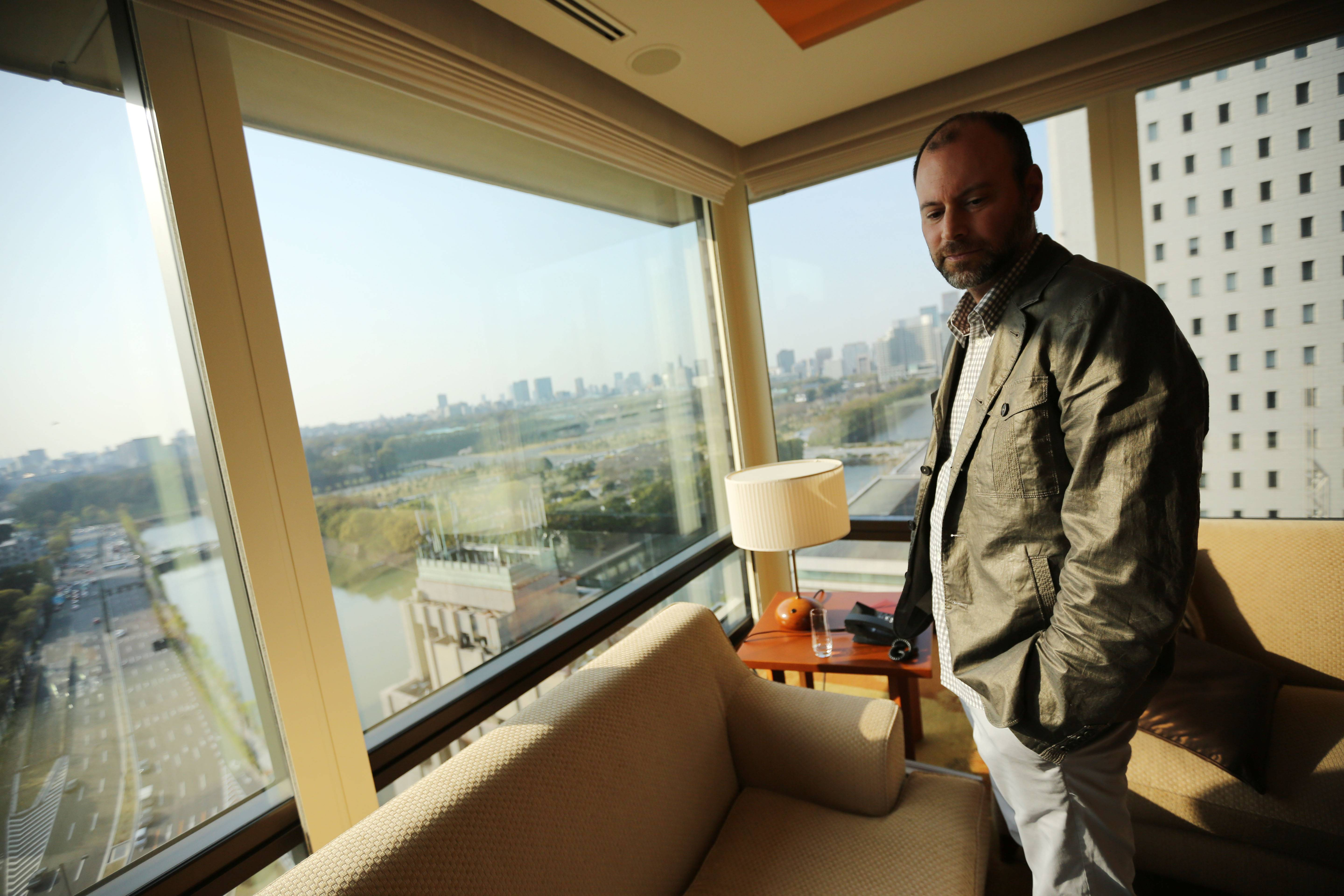 Noel Biderman, chief executive of Avid Life Media Inc., which operates AshleyMadison.com., by a hotel room window overlooking the Imperial Palace grounds during a photo session in Tokyo.
