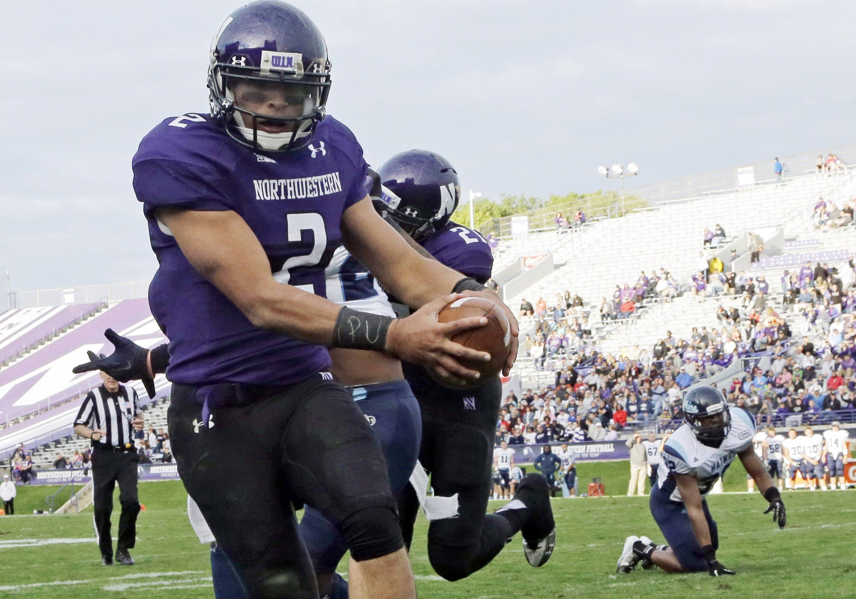 "In this Sept. 21, 2013, file photo, Northwestern quarterback Kain Colter (2), wears APU for ""All Players United"" on wrist tape as he scores a touchdown during an NCAA college football game against Maine in Evanston. The five-member regulatory board that will ultimately decide if Northwestern University football players can unionize has itself been in the middle of a firestorm."