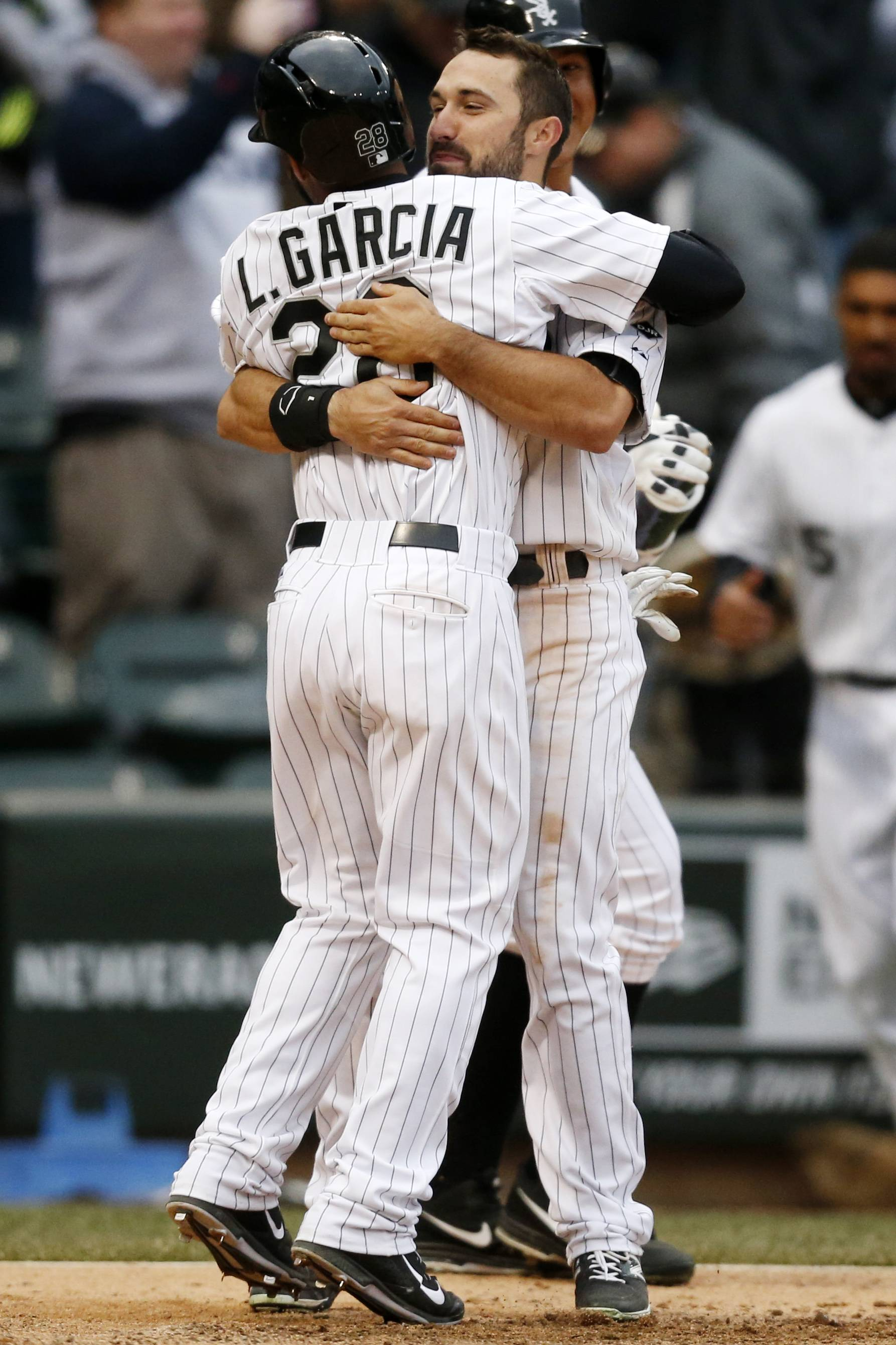 Chicago White Sox's Leury Garcia (28) celebrates with teammate Adam Eaton after scoring to end a baseball game in the 11th inning on Wednesday in Chicago. The White Sox won 7-6.