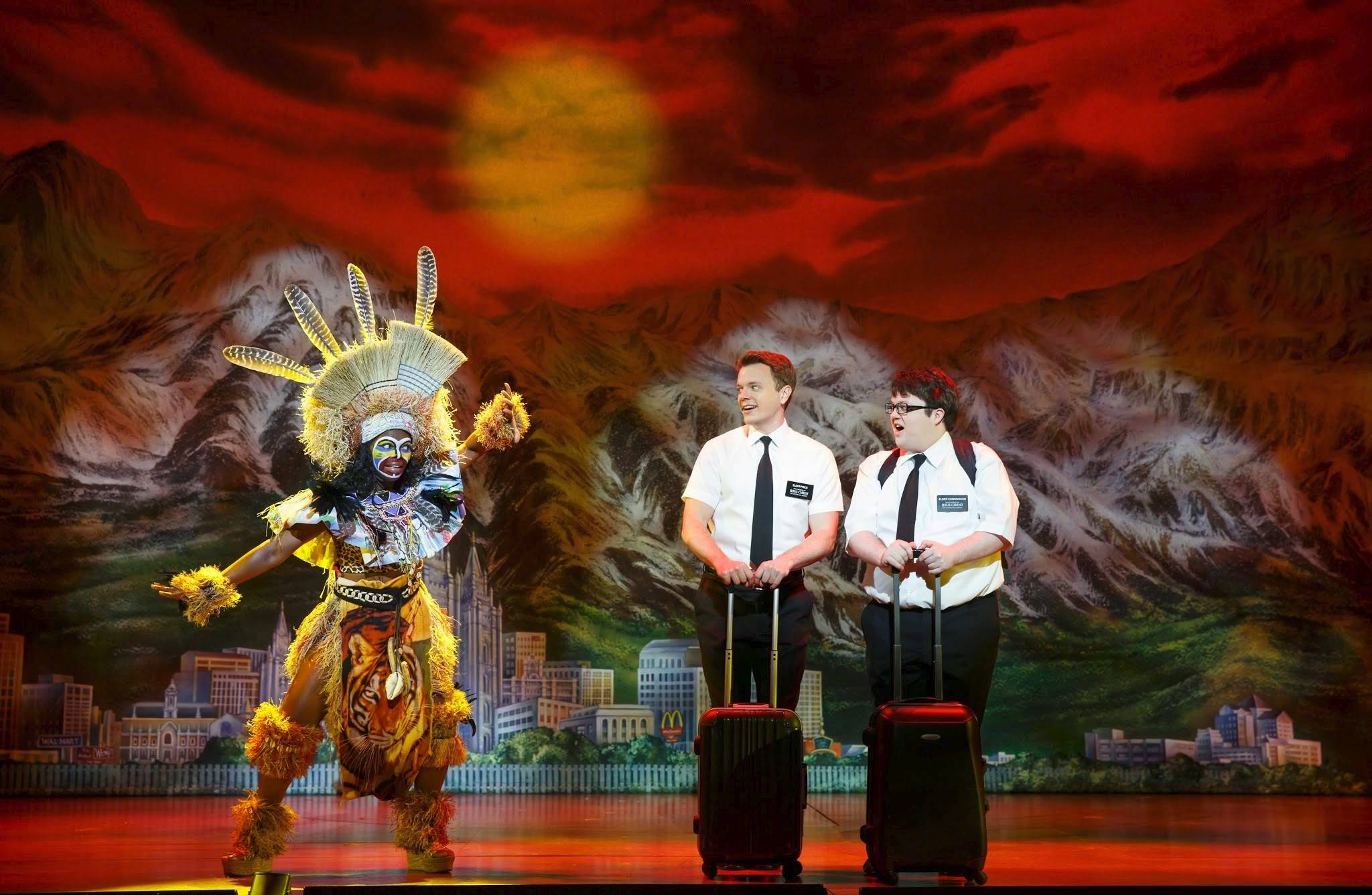 "Monica L. Patton appears in a ""Lion King""-inspired send off for Uganda-bound missionaries Elder Price (David Larsen) and Elder Cunningham (Cody Jamison Strand) in one of two national tours of the hit musical ""The Book of Mormon."" The adults-only Broadway show returns to Chicago's Bank of America Theatre Tuesday, Feb. 24, 2015."