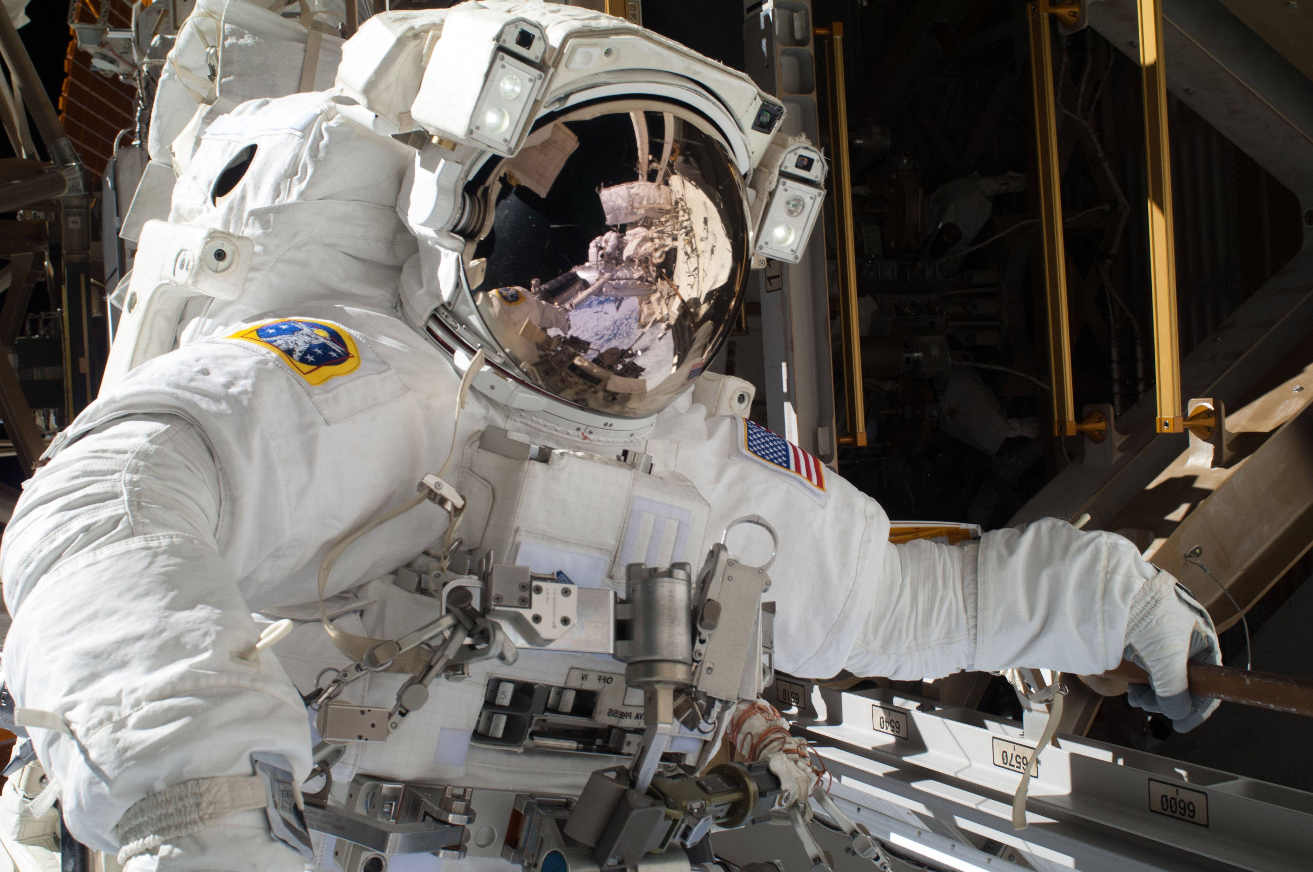 In December, astronaut Michael Hopkins works to repair an external cooling line on the International Space Station on a spacewalk 260 miles above Earth.