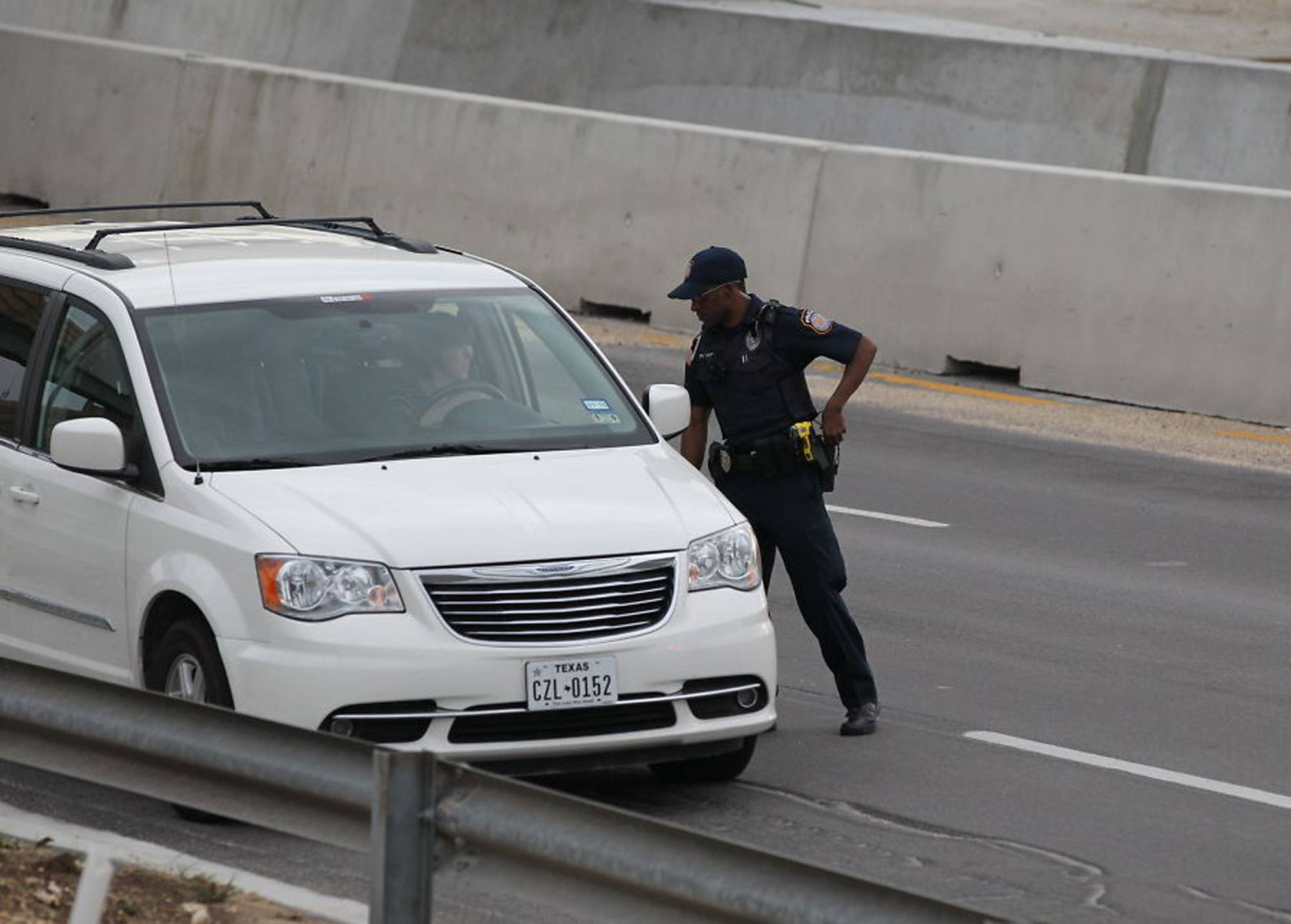 A police officer checks drivers' IDs outside the main gate at Fort Hood, Texas, after a shooting Wednesday at the Army base. One person was killed and at least 14 injured in a shooting Wednesday at Fort Hood.