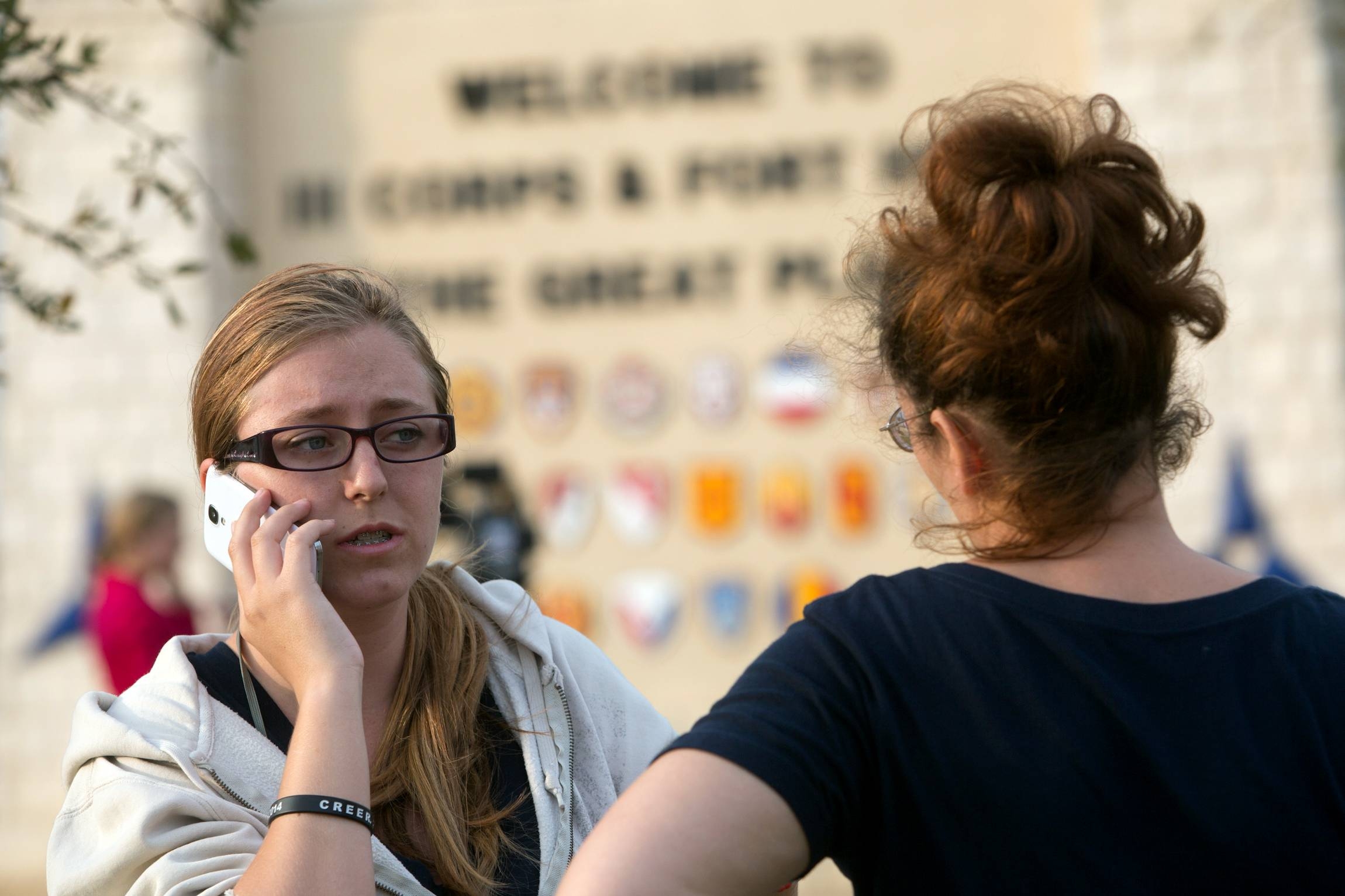 Krystina Cassidy, left, and Dianna Simpson attempt to make contact with their husbands who are stationed inside Fort Hood while standing outside of the Bernie Beck Gate on Wednesday in Fort Hood, Texas. One person was killed and 14 injured in the shooting, and officials at the base said the shooter is believed to be dead.