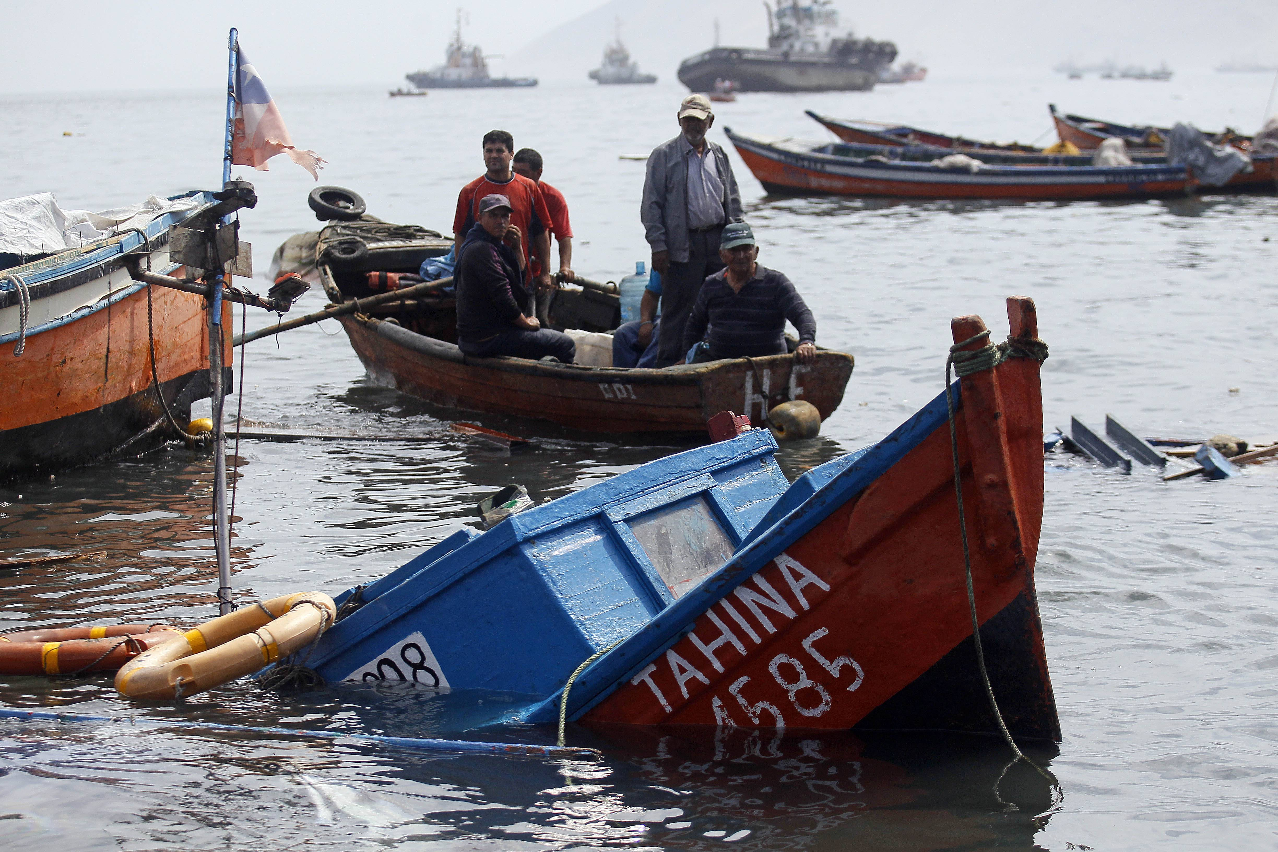Fishermen look for boats to salvage that were damaged overnight in the port of Iquique, Chile, Wednesday. Chilean authorities discovered surprisingly light damage Wednesday from a magnitude-8.2 quake that struck in the Pacific Ocean Tuesday.