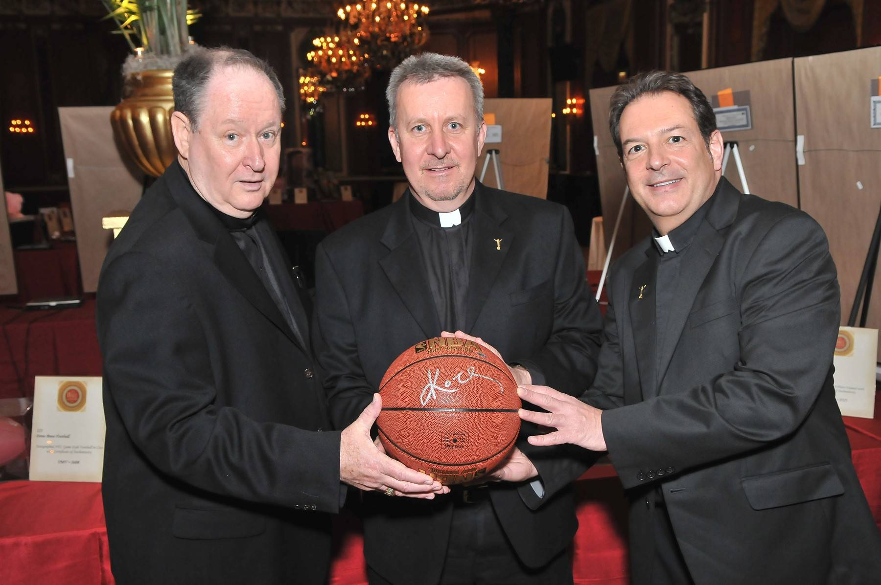 This Kobe Bryant-autographed basketball was a prize auction item at the 2013 ball. Holding it are Daniel McCormick, C.F.A., Provincial Immaculate Conception Province, Brother Paul Magner and Brother Tom Klein C.F.A.