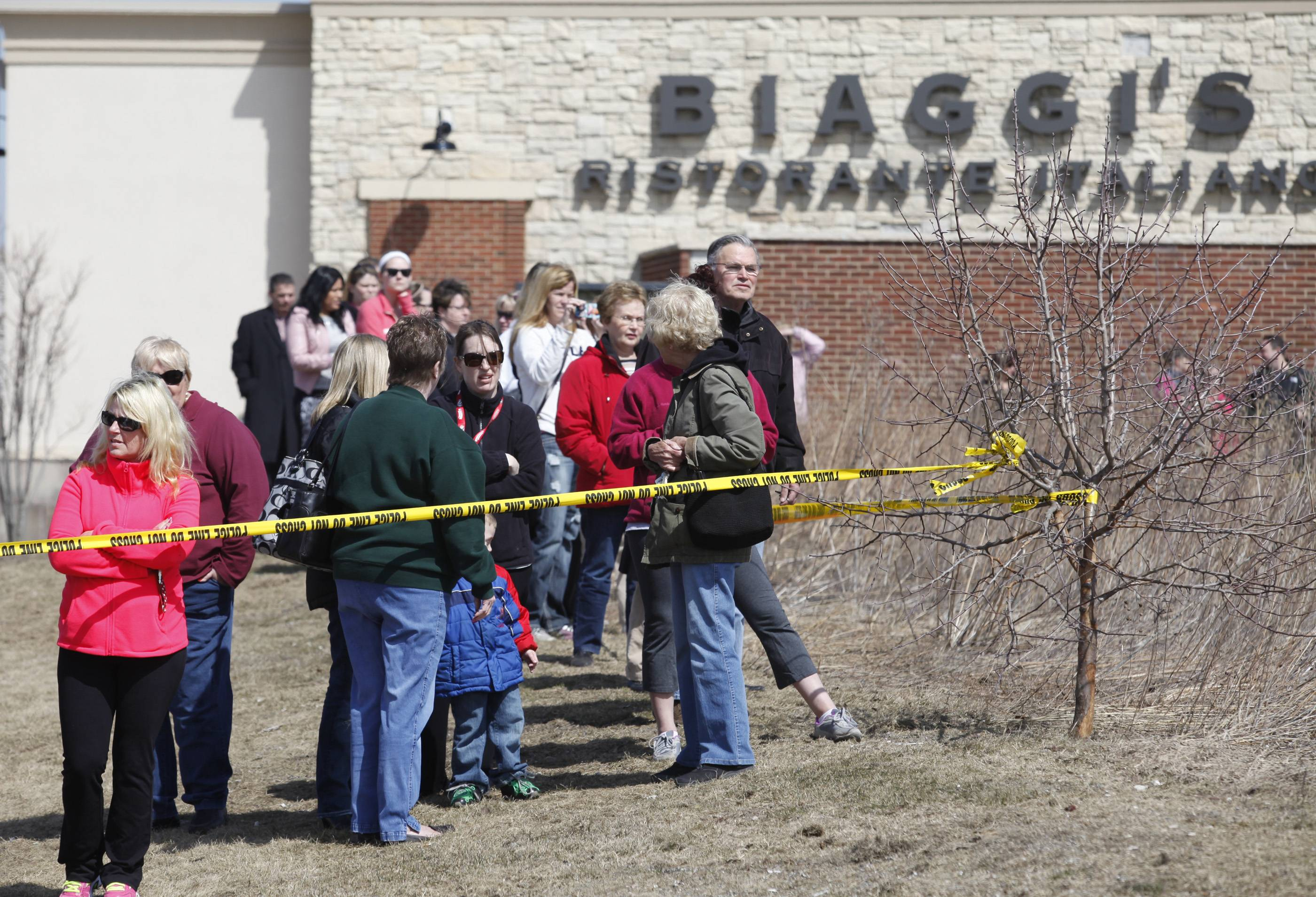 Curious onlookers at Algonquin Commons watch from behind the police tape Wednesday after a car wound up in the pond.