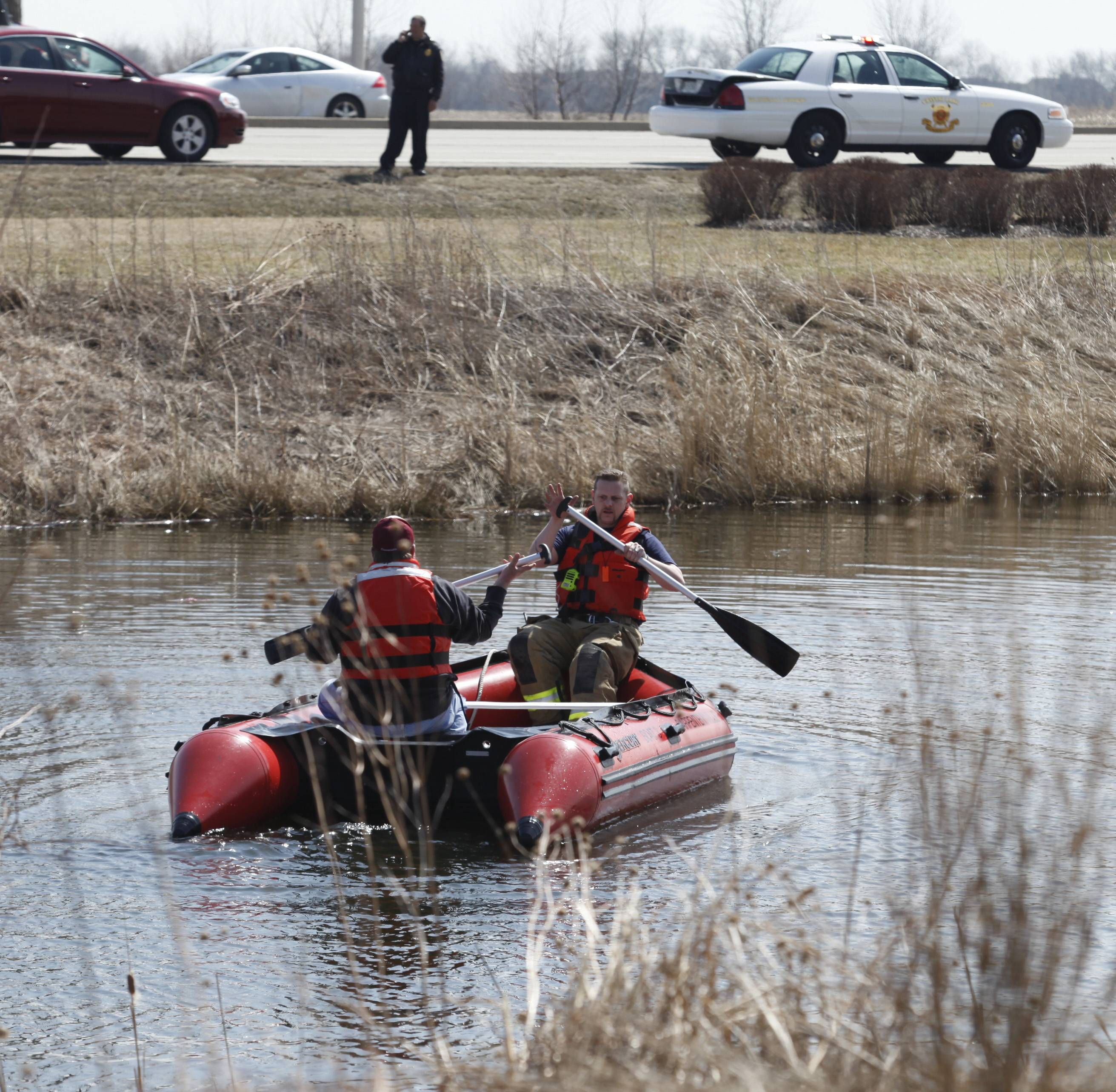 Firefighters continue to search a pond near Algonquin Commons Wednesday after a car went into the pond and the driver had to be rescued. Algonquin resident Paul Mellor, 57, the car's driver, was unconscious and not breathing when first responders pulled him from the sinking car.