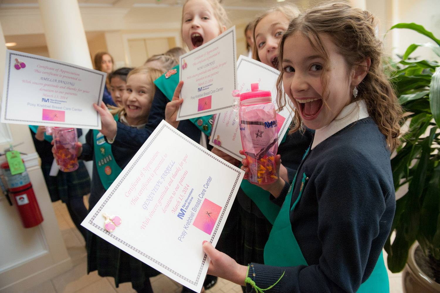 Members of the Junior Girl Scout Troop of Lake Forest Country Day School hold up certificates they were given by Northwestern Medicine in recognition of their donation of pillows for breast cancer patients.