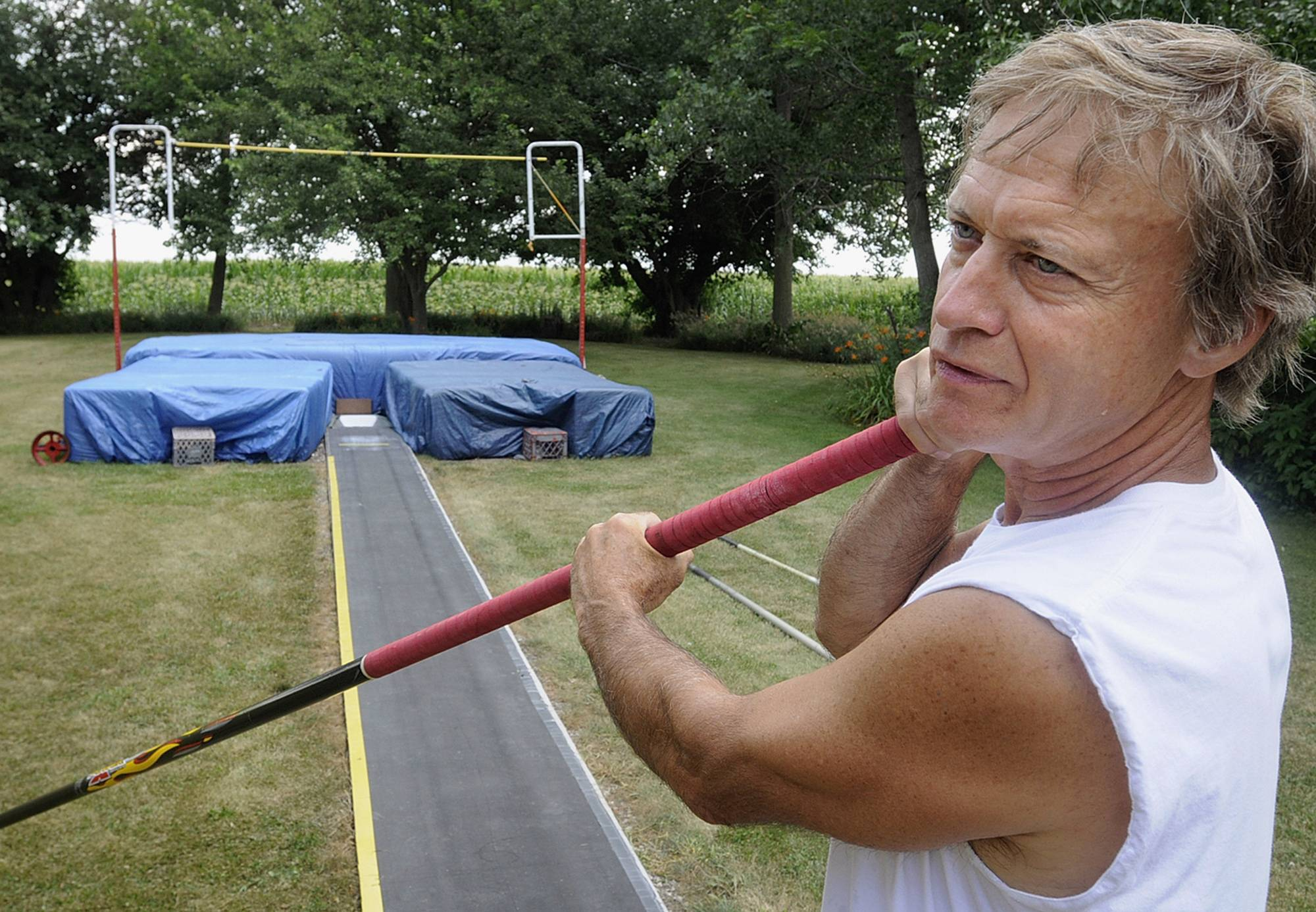 Larry LaGesse, prepares to pole vault in the backyard training center he built at his rural Chebanse, Ill., home.