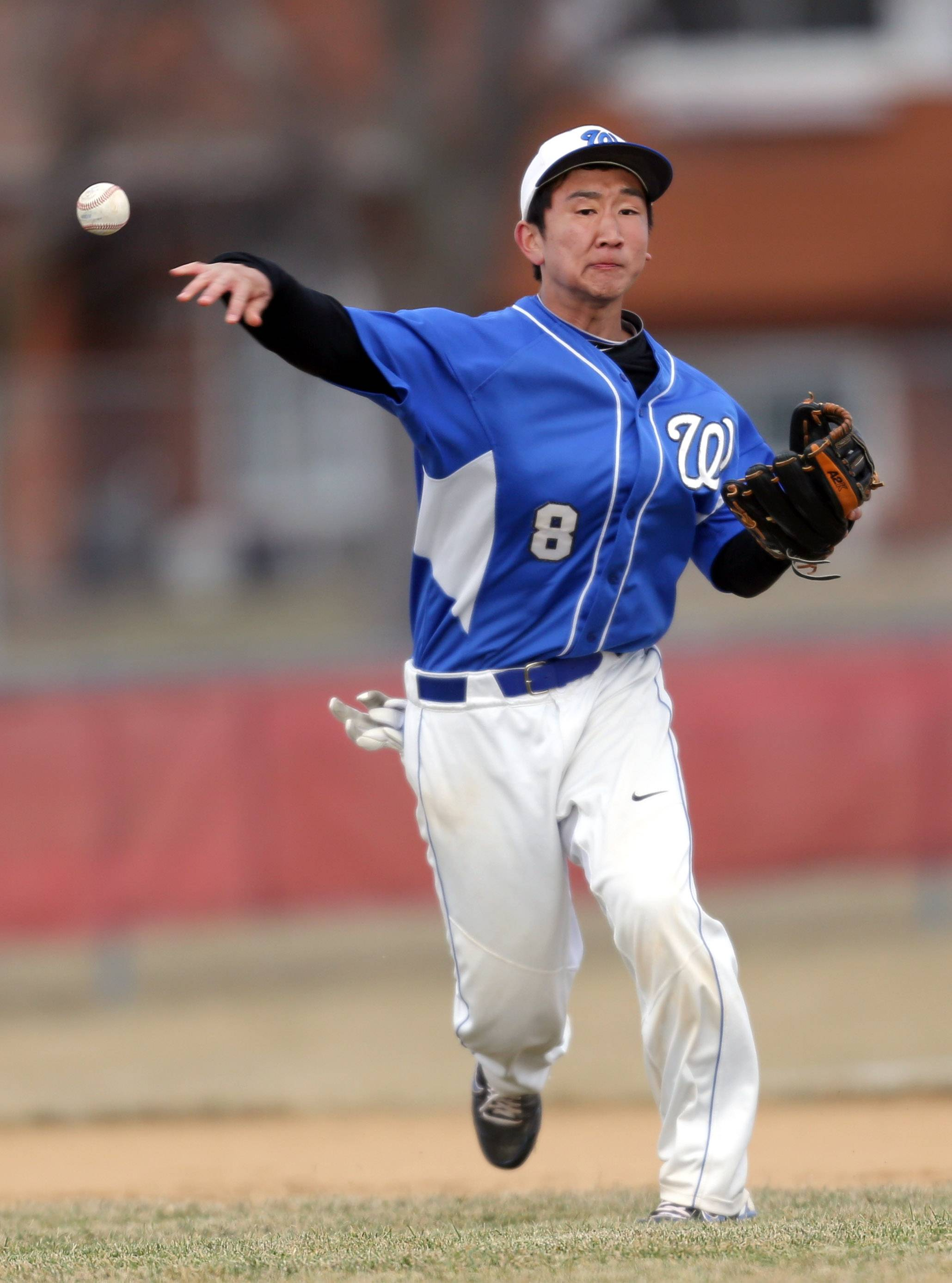 Wheeling's Josh Kim throws to first base against host Mundelein on Wednesday.