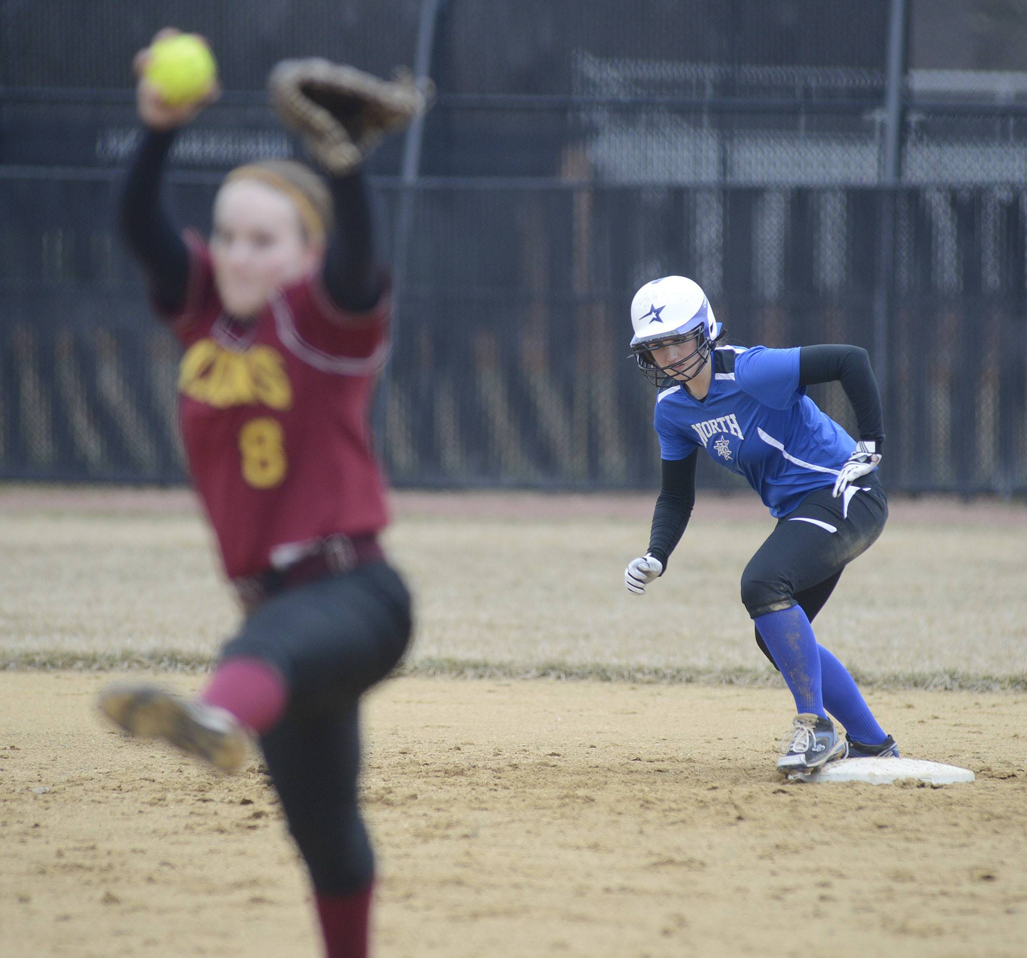 Laura Stoecker/lstoecker@dailyherald.comSchaumburg's Roxanne Kakareka pitches while St. Charles North's Abby Howlett leans off second base in the fourth inning on Wednesday, April 2.