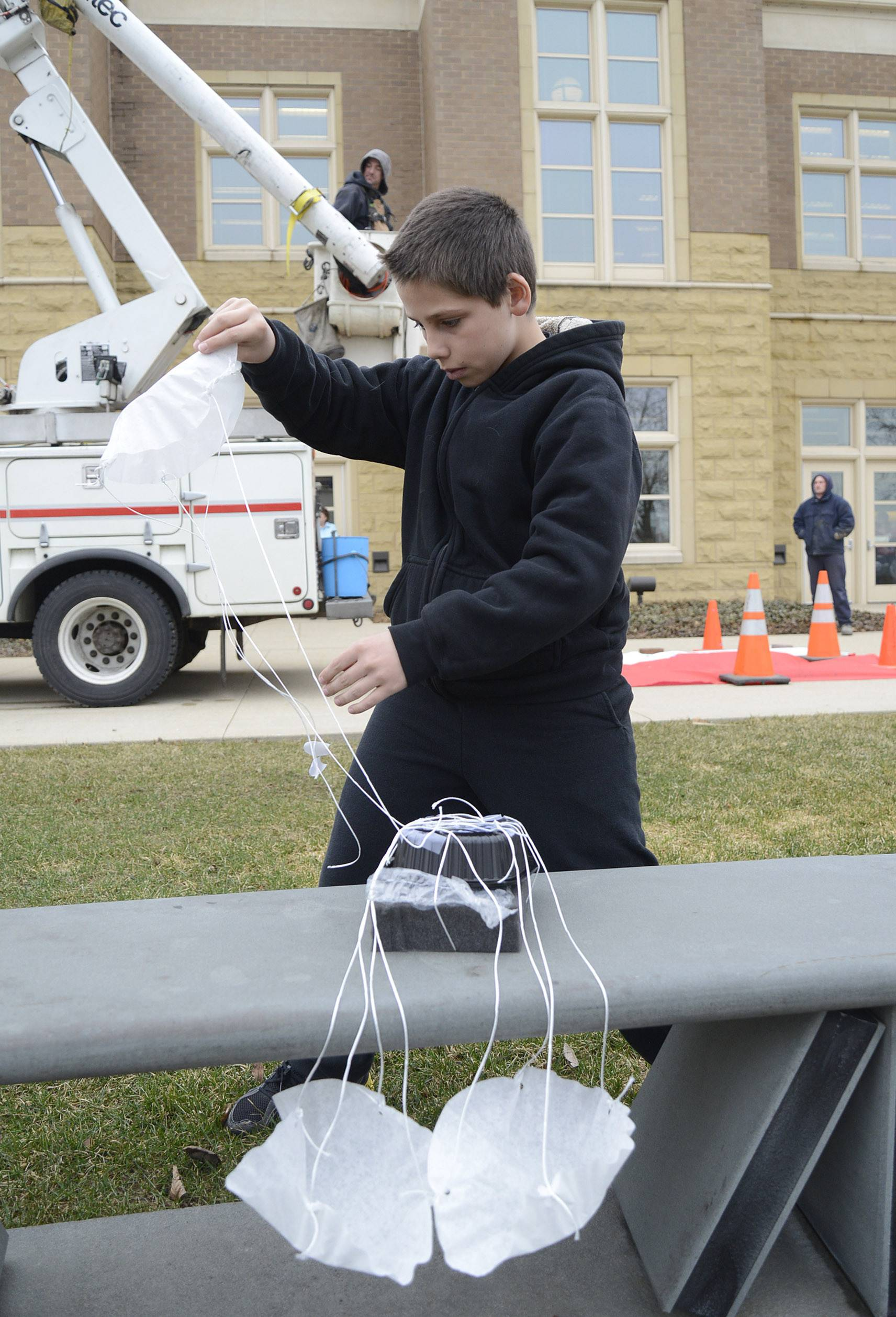 Benny Avila, 10, of Batavia preps his coffee filter parachute after inserting a raw egg into its protective casing for the egg drop competition Thursday at Batavia Public Library. A bucket truck from the city's electric department helped release the entries.