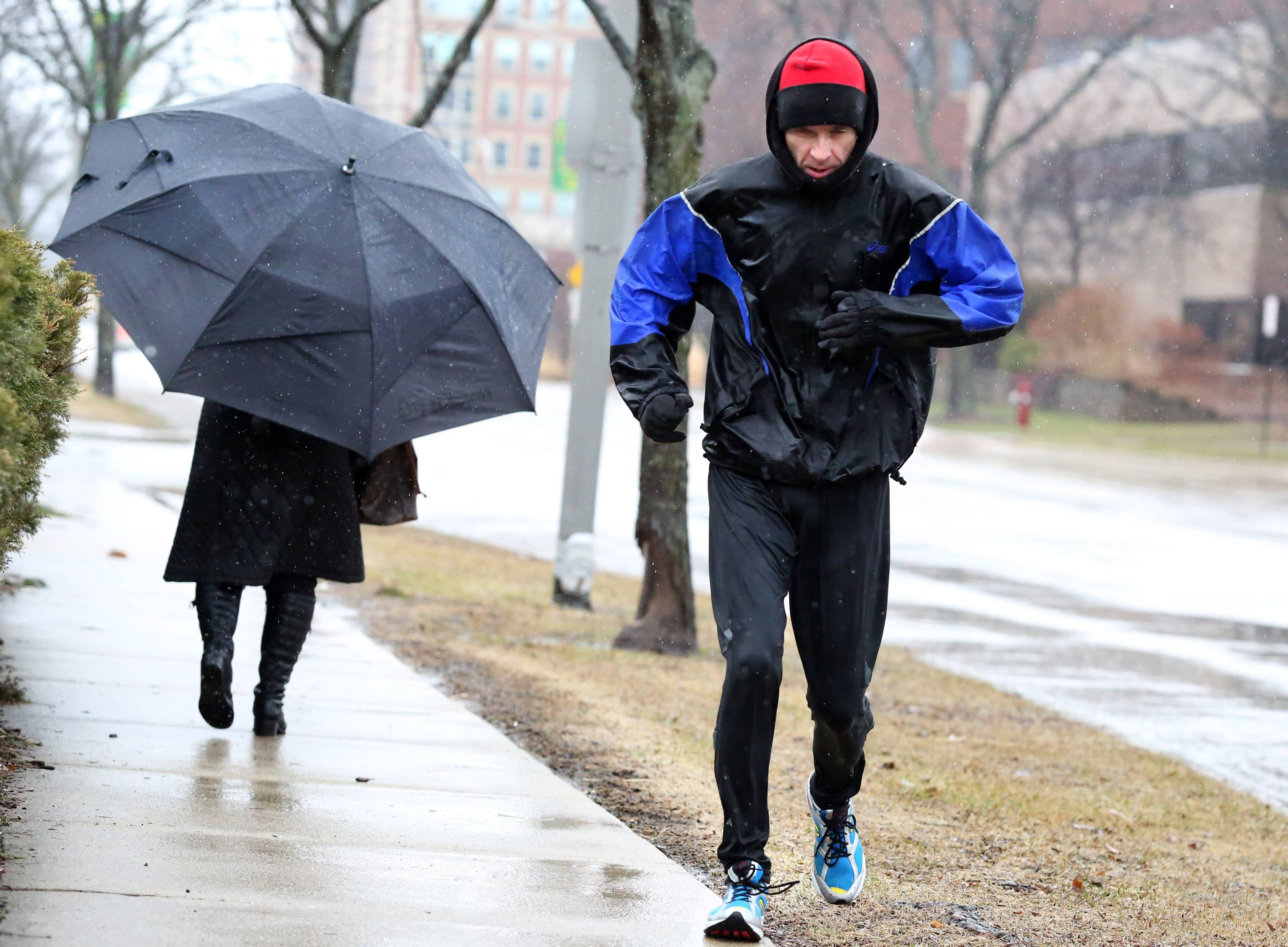 With his hands tucked in his jacket sleeves, Dave Raub of Arlington Heights runs a six-mile route through Arlington Heights in the rain on Thursday. He has run the exact same route almost every day for 31 years.