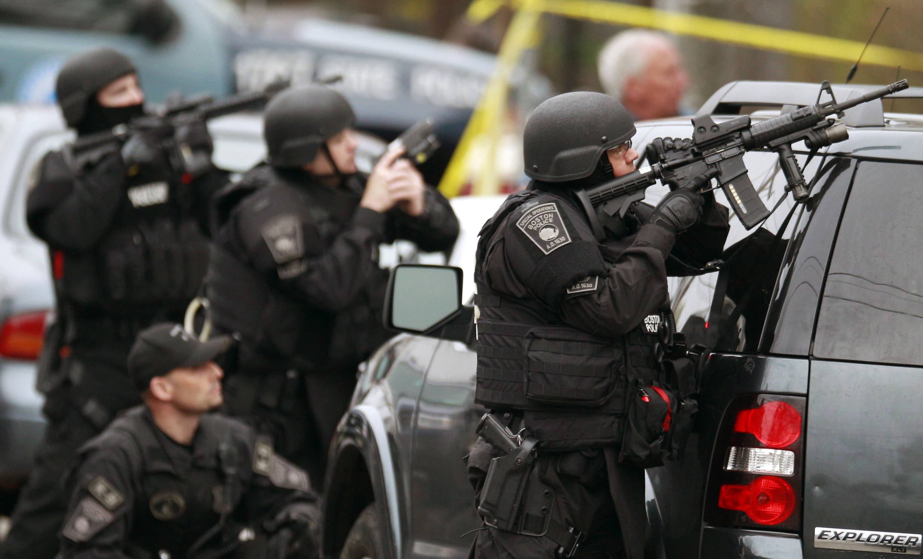 In this April 19, 2013 file photo, police in tactical gear surround an apartment building while looking for a suspect in the Boston Marathon bombings in Watertown, Mass. A Harvard University report released Thursday, April 3, 2014, on the response to the bombings was largely positive, but criticized law enforcement for the chaotic gunfight in which one suspect was killed and a police officer seriously injured because it lacked coordination.