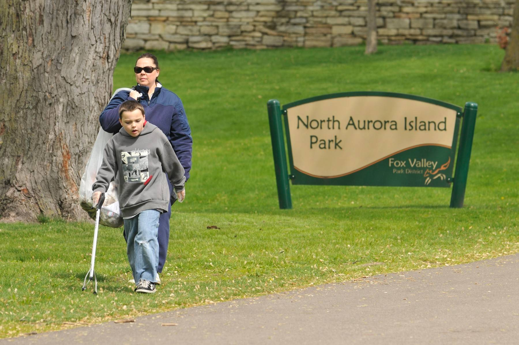 A pair of volunteers helps clean up along the Fox River Trail during a previous Spring Spruce-Up, which will be held Saturday, April 26, at four park sites.