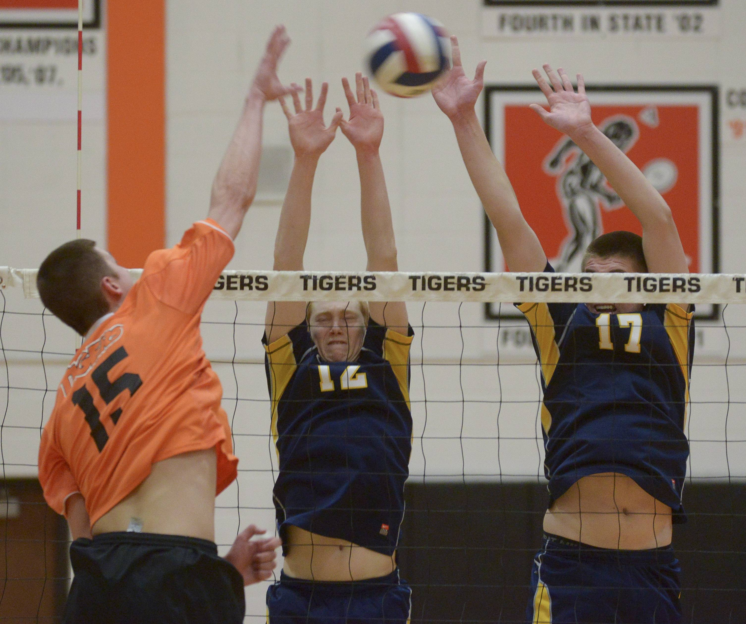 Wheaton Warrenville South's Jared Wilcox attempts to shoot one past Neuqua Valley's Tim Wagner and Brian McKissick during in boys varsity volleyball in Wheaton.