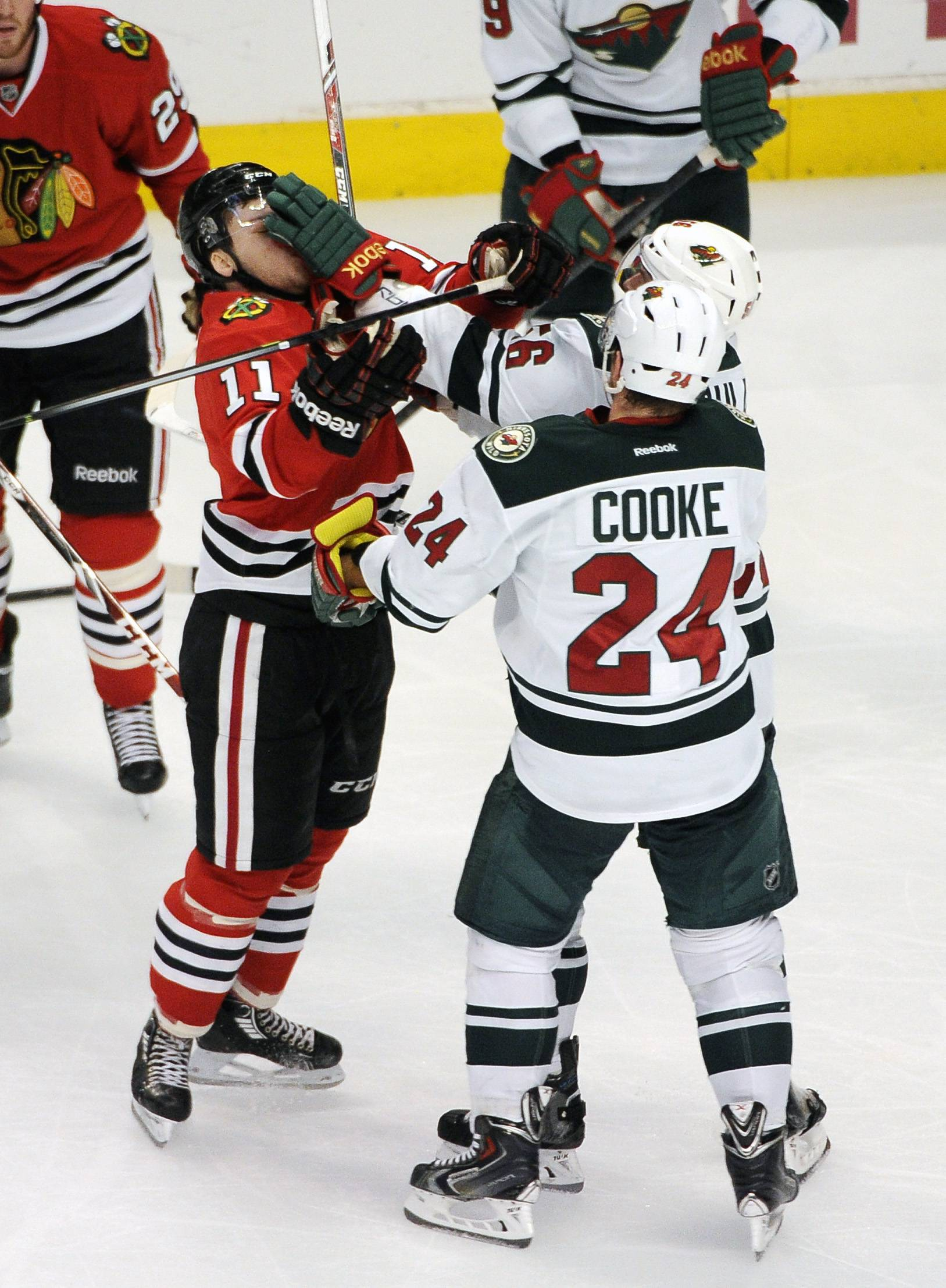 The Blackhawks' Jeremy Morin (11) gets a glove in the face from Minnesota Wild's Erik Haula (56) in the second period of the game in Chicago Thursday.