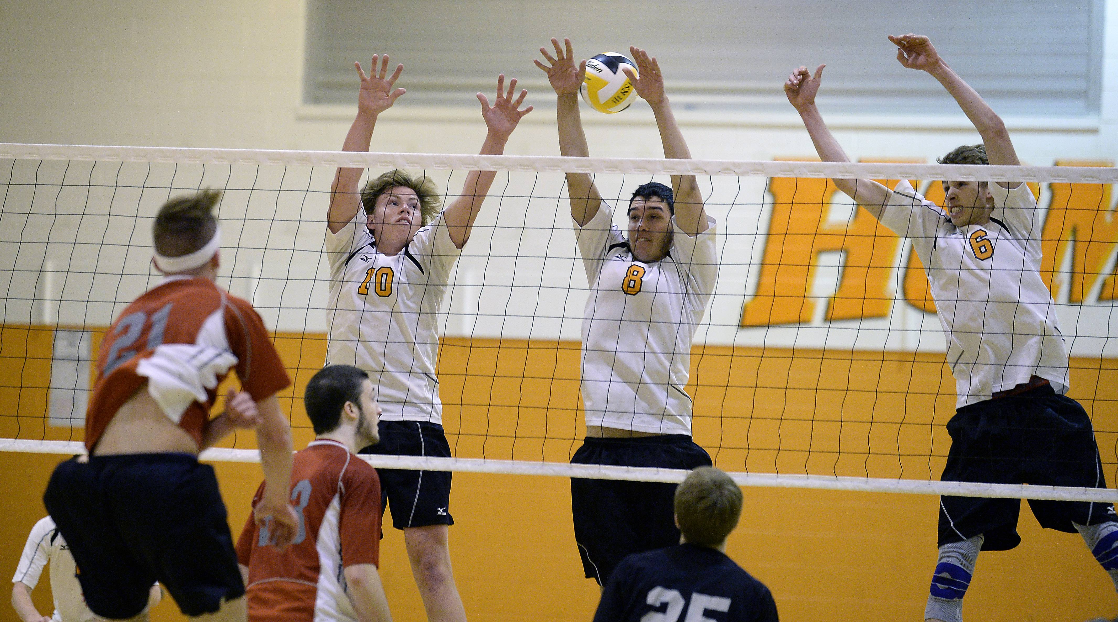 Palatine's Jacob Niedzwicki fires one through the arms of Hersey's defensive wall of Matt Torvik, Jordan Saeed and Bart Migus in game one of the boys varsity volleyball at Hersey High School on Thursday.