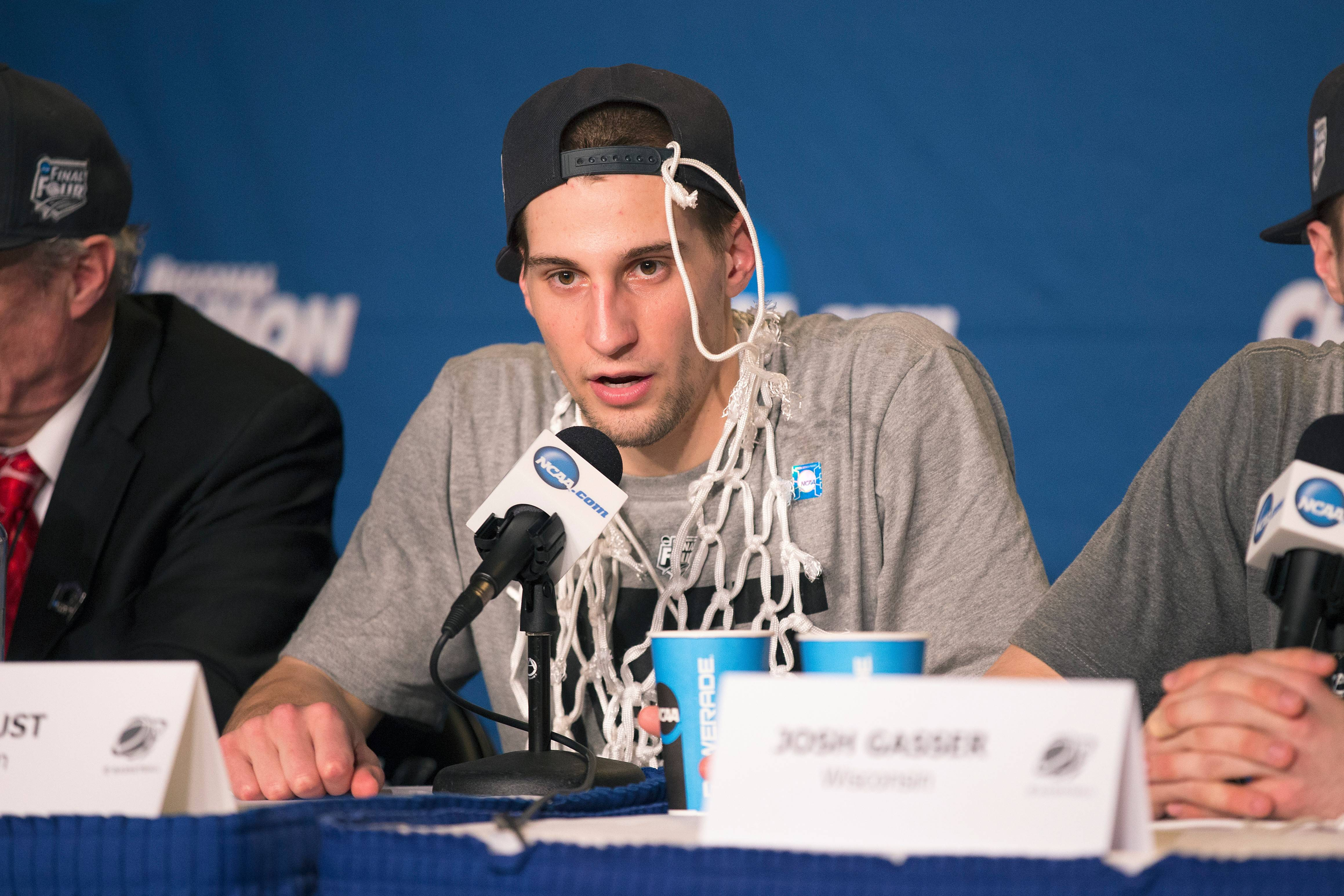 Wisconsin guard Ben Brust talks to the media after the West region victory against Arizona — with a piece of the elusive net hanging from his cap.